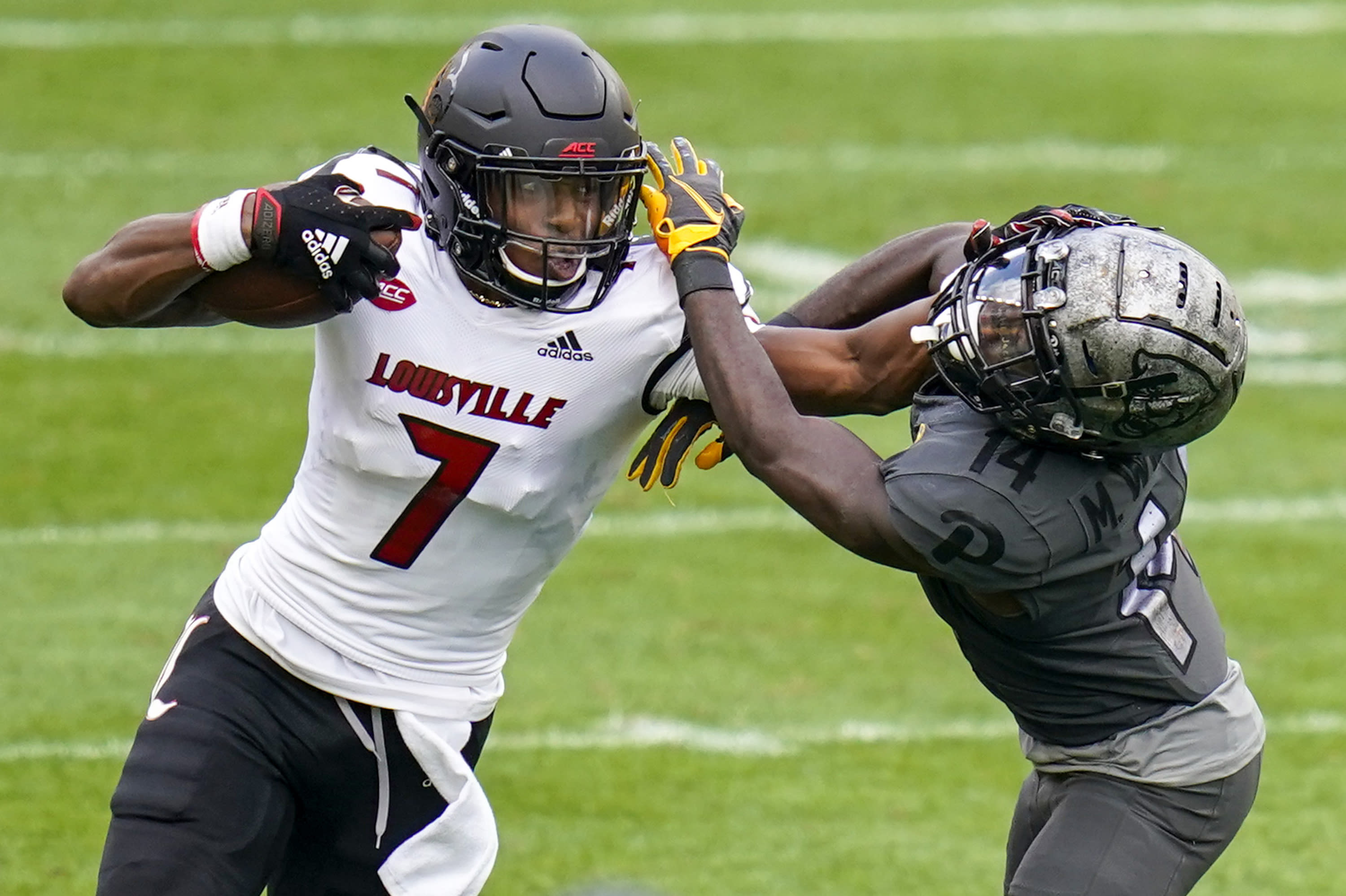 Louisville wide receiver Dez Fitzpatrick (7) stiff-arms Pittsburgh defensive back Marquis Williams (14) as he tries for more yards after a catch during the second half of an NCAA college football game, Saturday, Sept. 26, 2020, in Pittsburgh. Pittsburgh won 23-20. (AP Photo/Keith Srakocic)