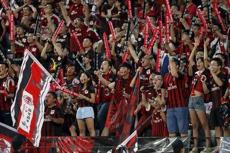Chinese fans of AC Milan cheer their team during the International Champions Cup friendly match against Inter Milan in Shenzhen