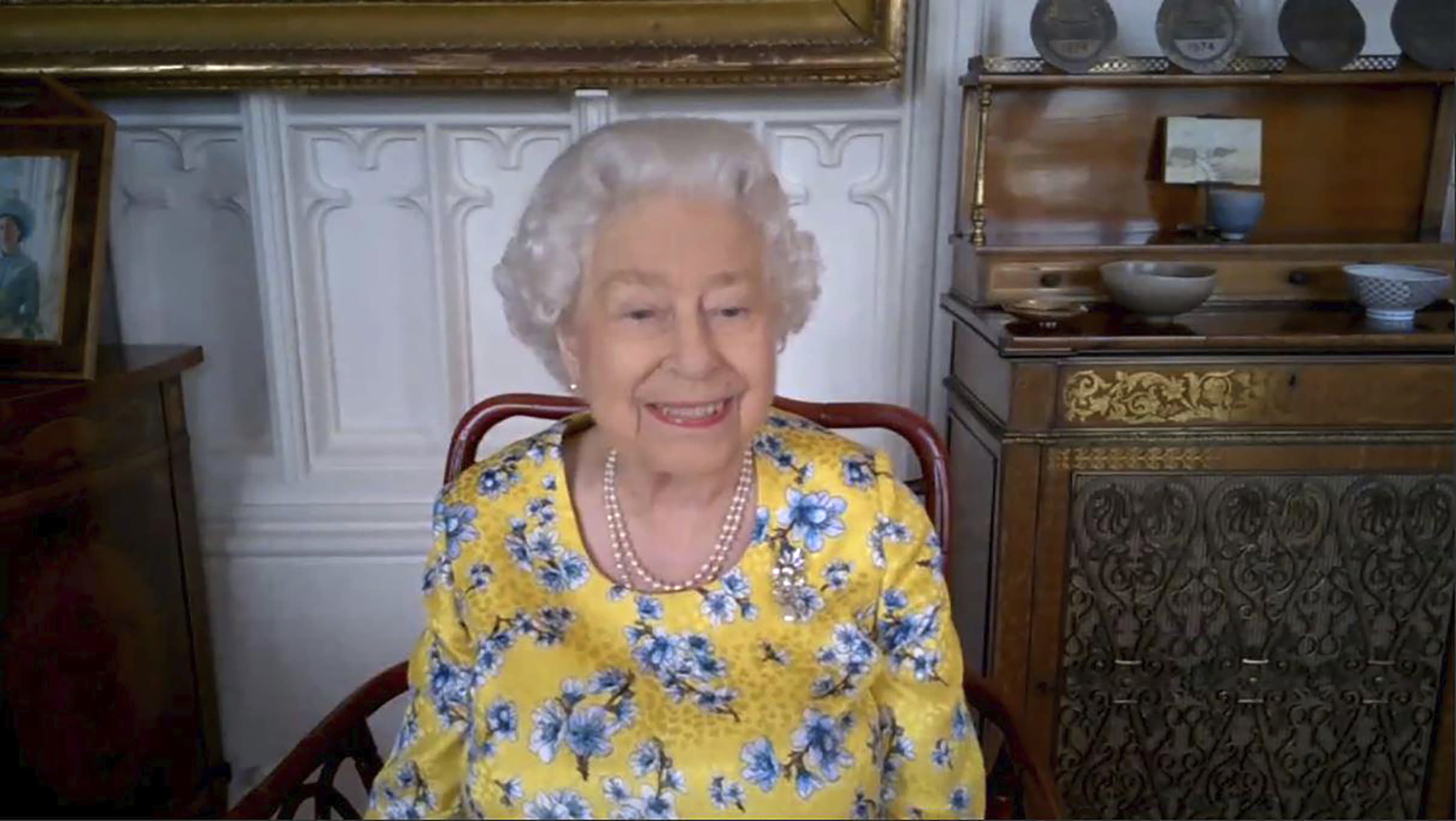 Undated handout photo released Saturday July 25, 2020, by the Royal Communications, showing Britain's Queen Elizabeth II in Windsor, England, during a video link call for a 'virtual' visit to the Foreign and Commonwealth Office, FCO, to speak to members of staff and watch the official unveiling of a new portrait of herself by artist Miriam Escofet. The painting was commissioned by the Foreign and Commonwealth Office (FCO), as a 'lasting tribute to her service' to diplomacy. The Queen paid a virtual visit to the FCO via video call, to hear about their response to the COVID-19 outbreak and join the unveiling of the new portrait. (Foreign and Commonwealth Office via AP)