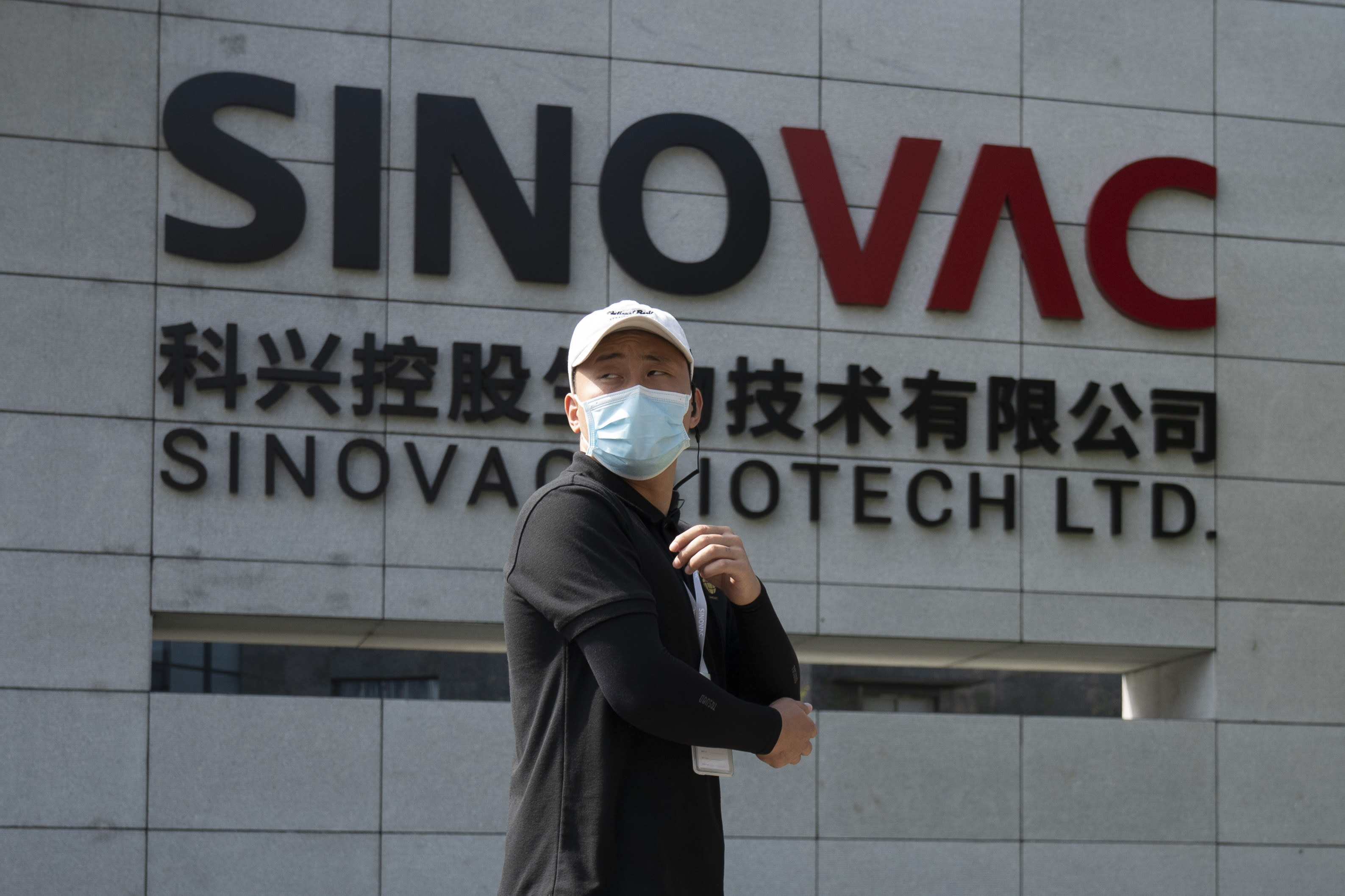 A worker passes by the logo outside the SinoVac vaccine factory in Beijing on Thursday, Sept. 24, 2020. SinoVac, one of China's pharmaceutical companies behind a leading COVID-19 vaccine candidate says its vaccine will be ready by early 2021 for distribution worldwide, including the U.S. (AP Photo/Ng Han Guan)