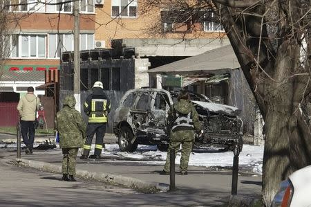 Members of the security and the emergency services work at the site of a car explosion, where Ukrainian state security service (SBU) officer Lieutenant Colonel Oleksandr Kharaberiush was killed, in the eastern port city of Mariupol, Ukraine March 31, 2017. REUTERS/Nikolai Ryabchenko