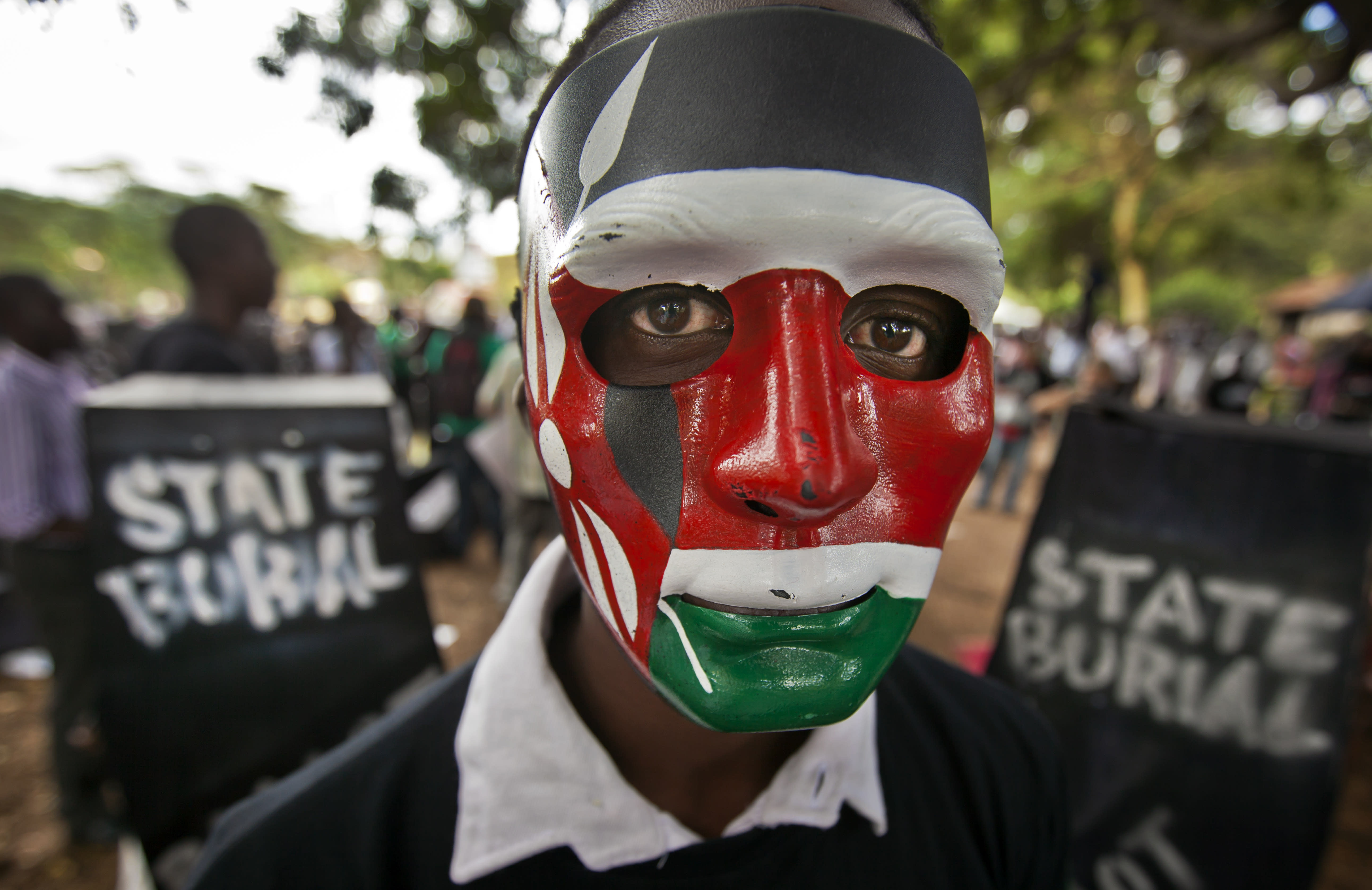 """A demonstrator wears a mask in the colors of the Kenyan flag as he stands next to mock coffins, on which are written """"State Burial, Ballot Revolution"""", before demonstrators carried the coffins to the Parliament and burned them, in Nairobi, Kenya Wednesday, Jan. 16, 2013. Hundreds of demonstrators angered at outgoing Kenyan legislators, whose term ended earlier this week and who earn about $175,000 a year in a country where the average annual income is $1,700, doused 221 mock coffins with gasoline, one for each legislator, to protest against last week's attempt to award themselves a $110,000 bonus, which was vetoed by the president. (AP Photo/Ben Curtis)"""