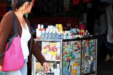 A woman walks past a stall selling medicines at Las Pulgas market in Maracaibo, Venezuela December 5, 2017. REUTERS/Isaac Urrutia
