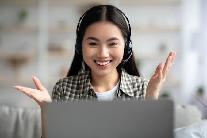 Emotional young asian lady having video call with friends, using laptop and headset at home, cheerfully talking and gesturing, closeup, copy space. Female student having online lesson