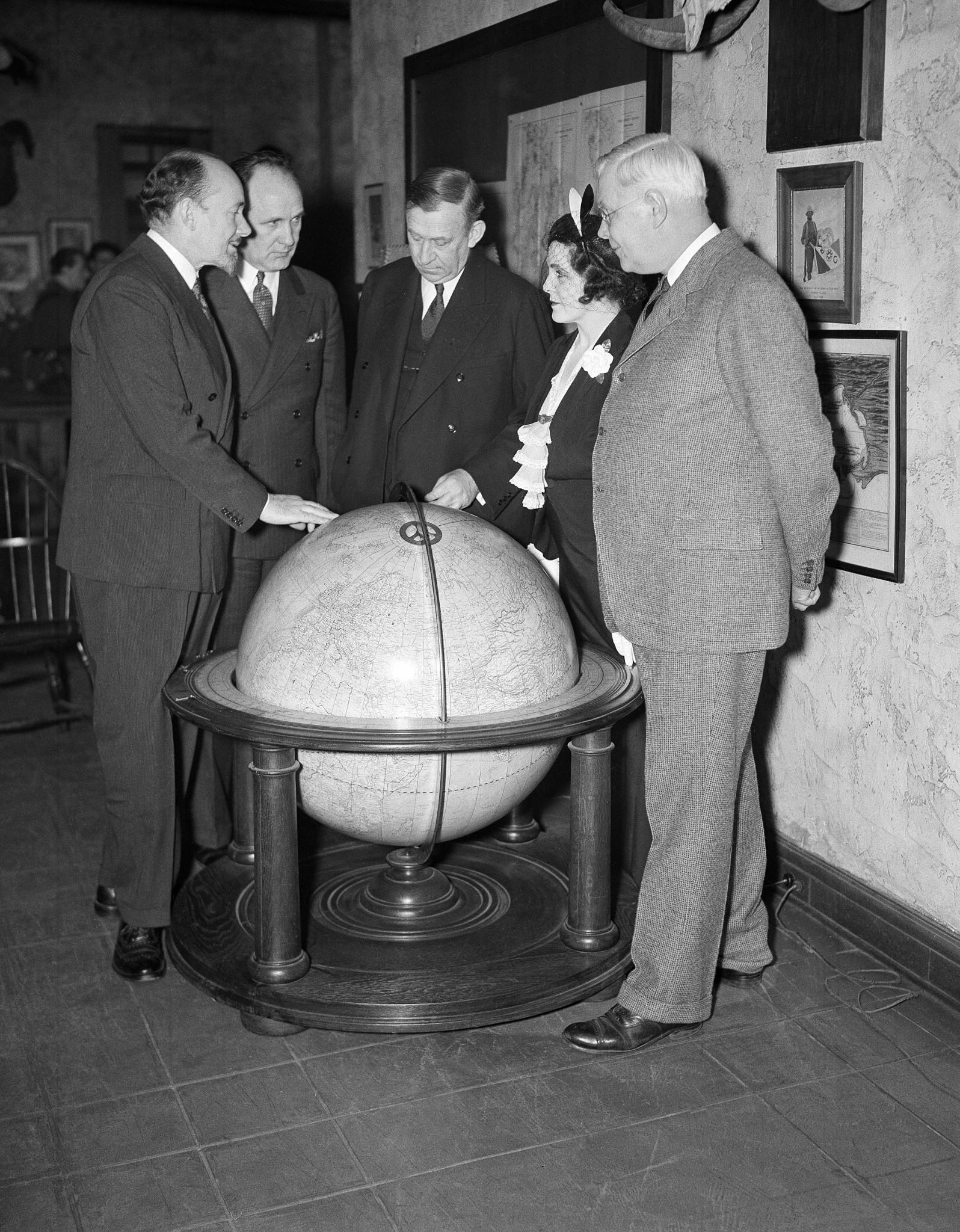 <p>Left to right: Sir George Hubert Wilkins, explorer and writer; Joseph Robinson, secretary of the Explorers' Club; Walter Granger, president of club; Lady Grace Drummond Hay, writer; and Dr. H. J. Spinden, director of the Brooklyn Museum, study the route of the Zeppelin Hindenburg's flight to America on a globe at the Explorers' Club in New York on May 10, 1936. (AP Photo/John Lindsay) </p>