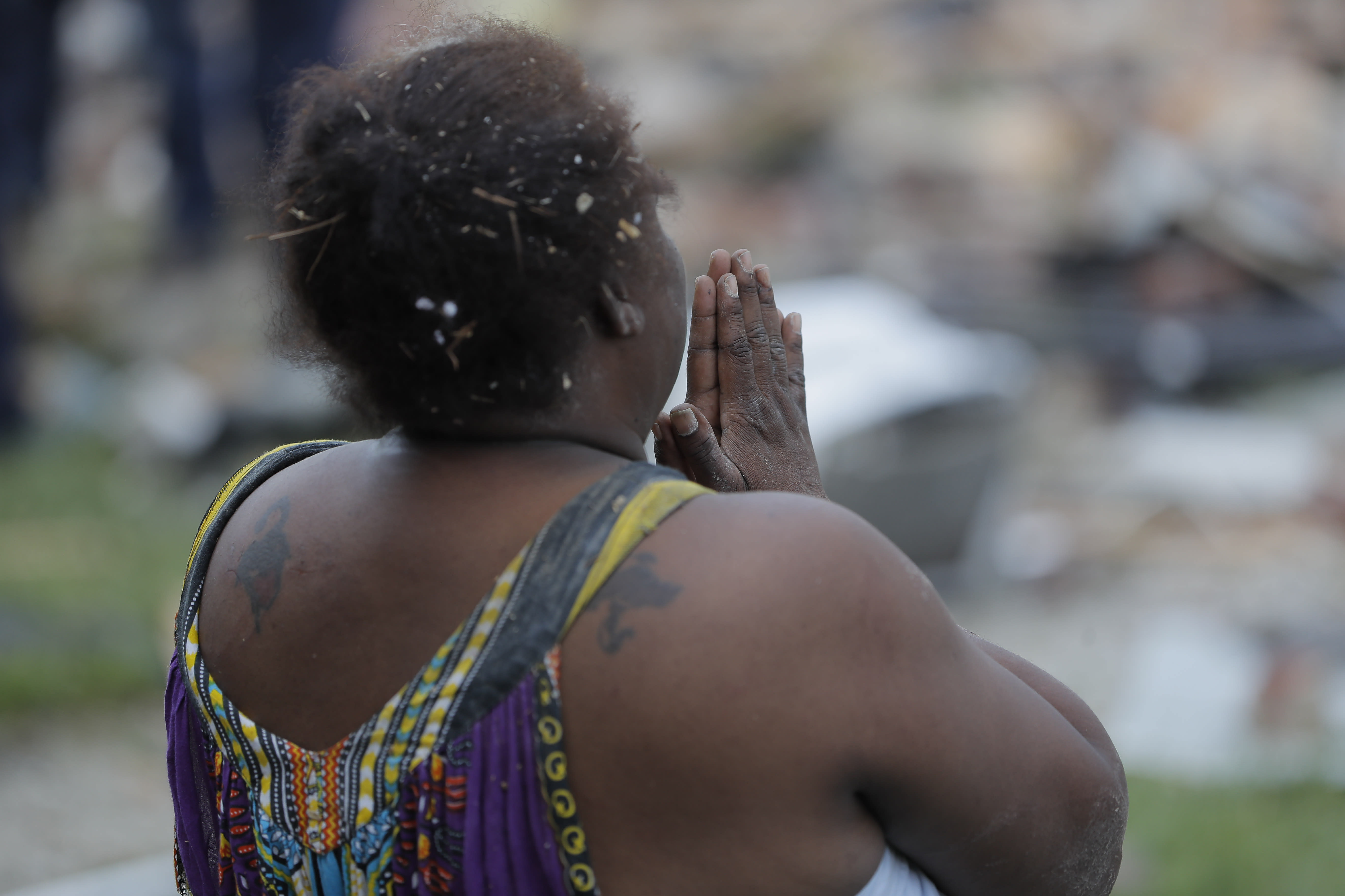 A woman stands in front of a pile of debris after an explosion in Baltimore on Monday, Aug. 10, 2020. Baltimore firefighters say an explosion has levelled several homes in the city. (AP Photo/Julio Cortez)