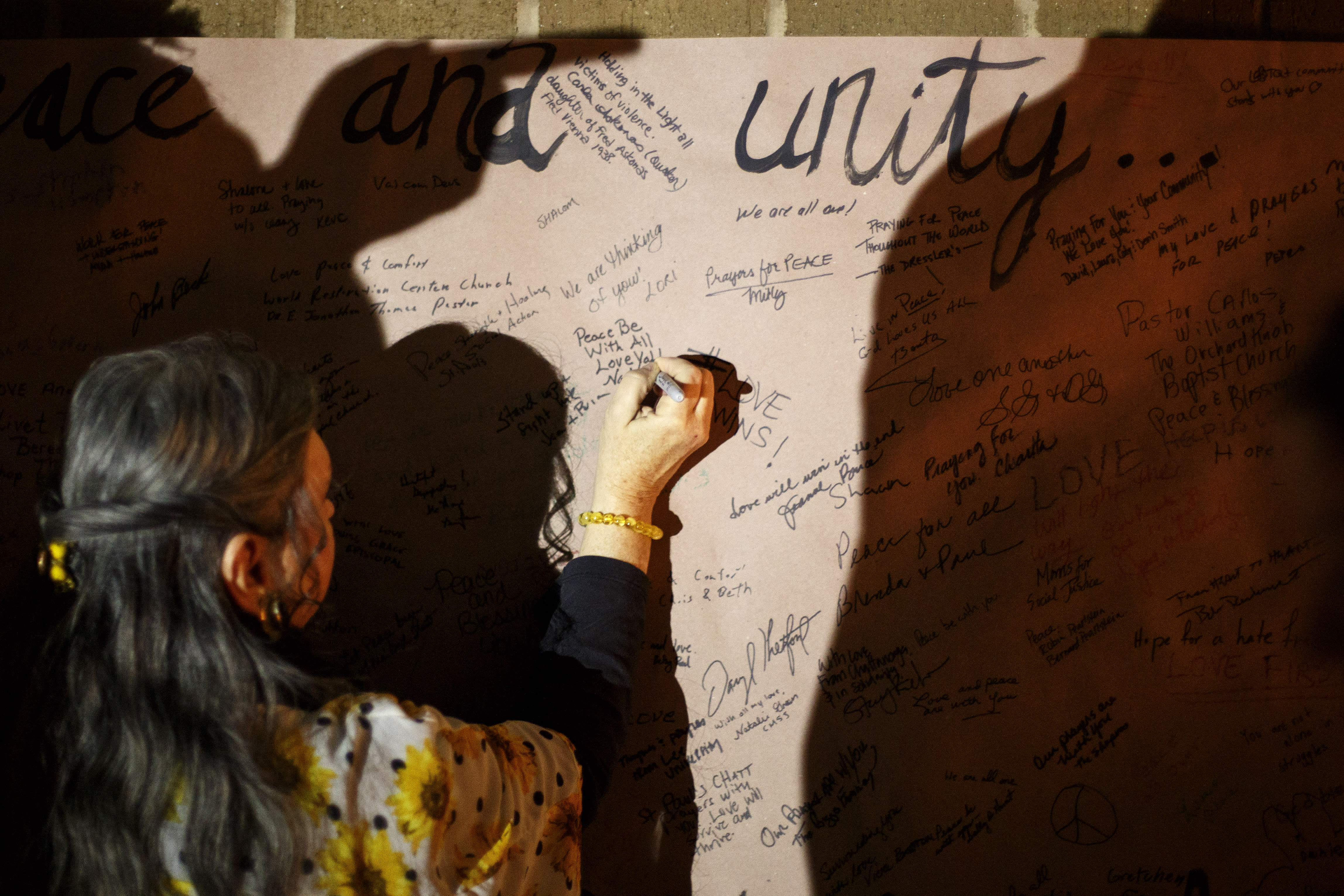 <p>Nada Joy Hyde writes a message of peace on a banner outside of the Jewish Cultural Center after a prayer vigil on Monday, Oct. 29, 2018 in Chattanooga, Tenn. The vigil was held for the victims of the shooting at the Tree of Life Synagogue in Pittsburgh. The vigil, open to all, included candle lighting, singing and words from various local faith leaders and Chattanooga Mayor Andy Berke. (Photo: C.B. Schmelter/Chattanooga Times Free Press via AP) </p>