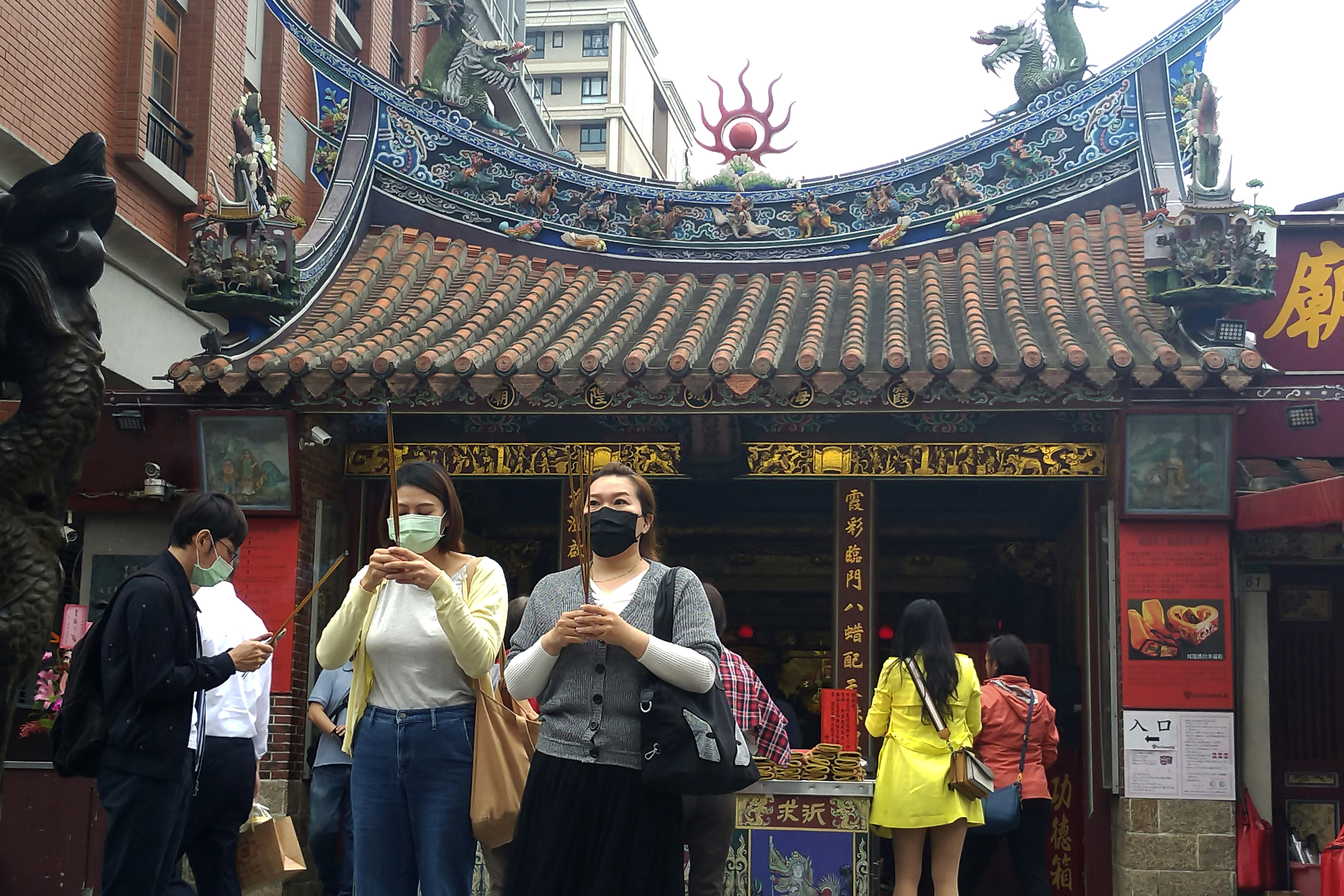 People wearing face masks to help curb the spread of the coronavirus hold insenses to pray at a temple in Taipei, Taiwan, Monday, Oct. 19, 2020. (AP Photo/Chiang Ying-ying)