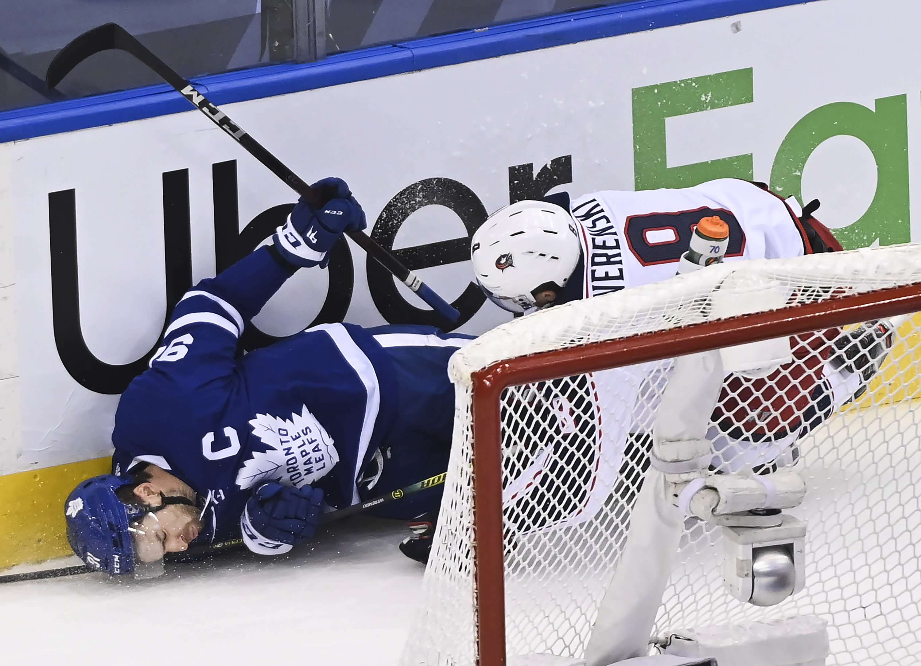 Columbus Blue Jackets defenseman Zach Werenski (8) takes out Toronto Maple Leafs centre John Tavares (91) during the first period of an NHL hockey playoff game Sunday, Aug. 9, 2020, in Toronto. (Nathan Denette/The Canadian Press via AP)
