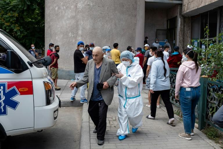 An elderly man is aided outside a medical facility in Bishkek -- many people say a lack of tests of poor quality tests are keeping the official virus case tally low (AFP Photo/DANIL USMANOV)