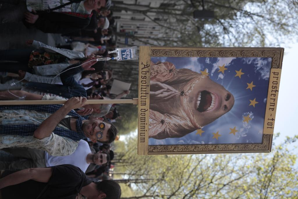 """A protester holding a placard showing a caricature of the French president and reading """"Absolute Power"""" in Latin, takes part in a demonstration on April 19, 2018 in Paris against government policies amid a rail strike and student sit-ins (AFP Photo/-)"""