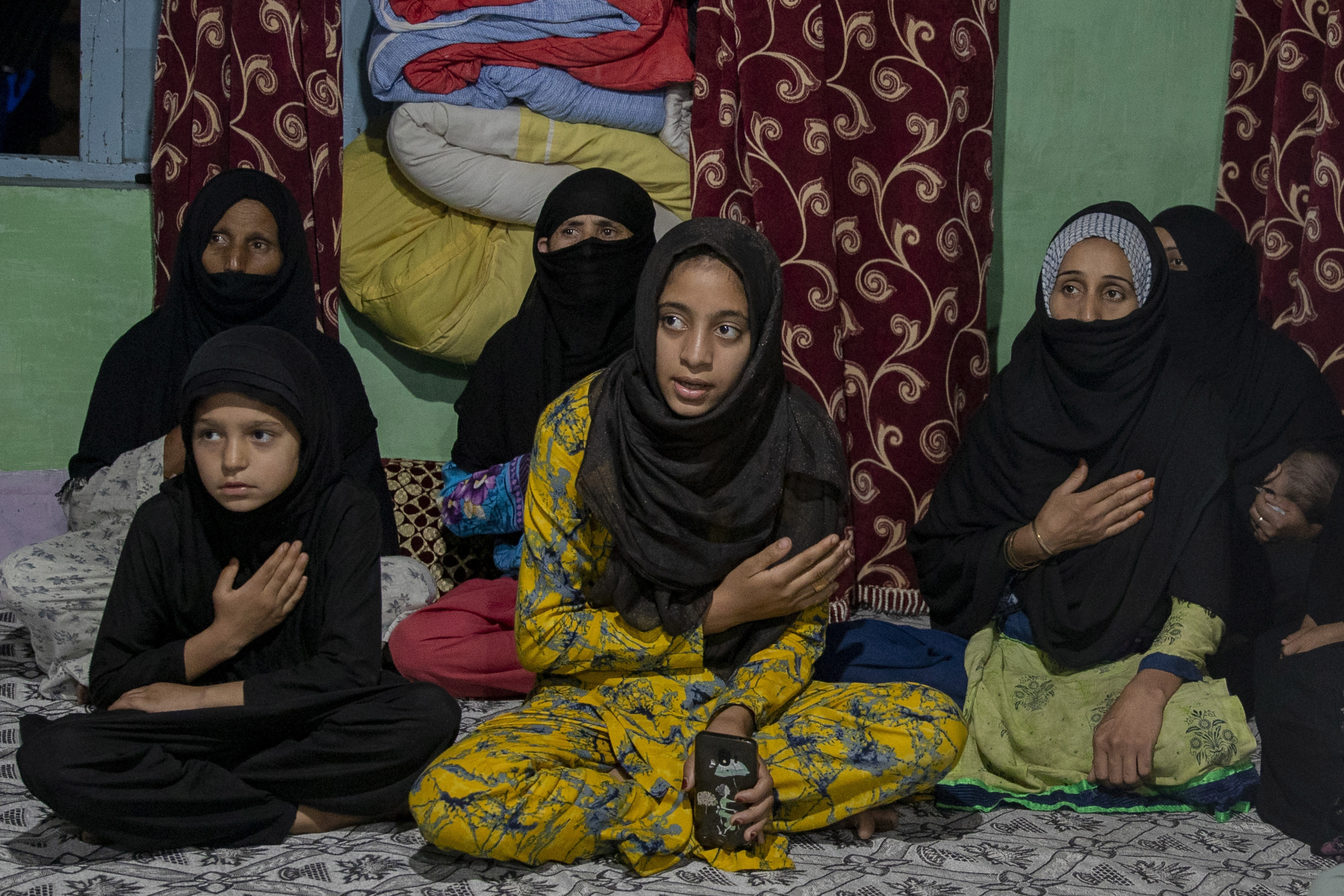 Kashmiri Shiite Muslims beat their chest as they watch religious broadcast on cable television to commemorate Muharram inside a residential house in the interiors of Dal Lake in Srinagar, Indian controlled Kashmir, Monday, Aug. 24, 2020. Observing the Muslim month of Muharram, which marks the martyrdom of the Prophet Muhammad's grandson in the battle of Karbala, is an article of faith. But as the coronavirus spreads in Indian-controlled Kashmir, Shiite Muslims prefer to commemorate the holy days inside their home following the advice of religious scholars and health experts in the disputed region's main city. (AP Photo/Dar Yasin)