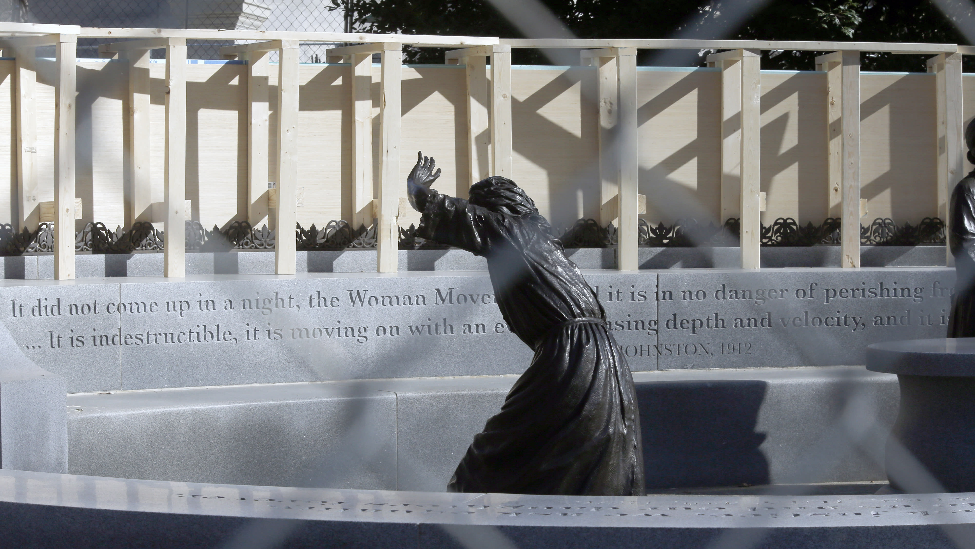 The statue of pioneer woman Laura Ingles is shown behind the fencing put up around the Virginia Women's Memorial on Capitol Square in Richmond, Va., Friday, Jan. 17, 2020. The fencing was to protect the monuments from the large crowd expected for the pro-gun rally Monday, Jan. 20. (Bob Brown/Richmond Times-Dispatch via AP)