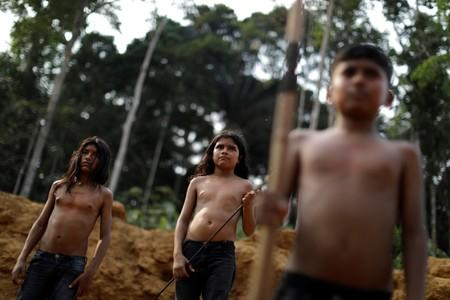Indigenous people from the Mura tribe react in front of a deforested in unmarked indigenous lands inside the Amazon rainforest near Humaita