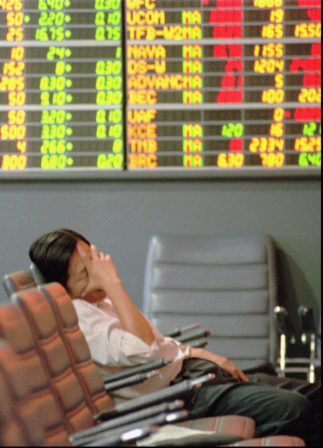 FILE- In this Nov. 21, 1997, file photo a Thai stock investor falls asleep while lonely monitoring a trading board at a stock house in the Stock Exchange of Thailand in Bangkok. A financial crisis that began in 1997 after Thailand devalued its currency against the U.S. dollar eventually sent markets reeling across the region in what became known as the Asian financial crisis. (AP Photo/Thaksina Khaikaew, File)