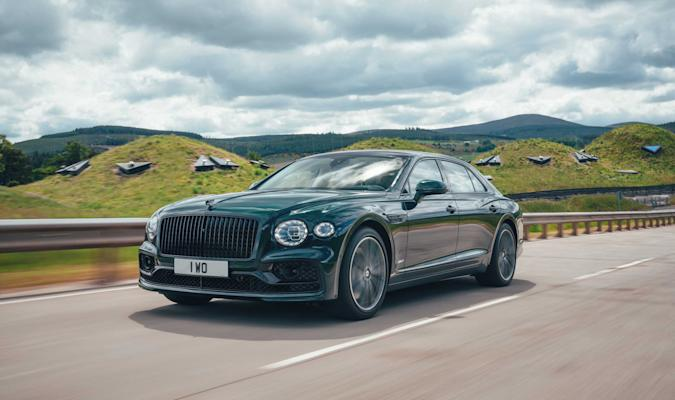 The Bentley Flying Spur plug-in hybrid drives down a highway with hills in the background.