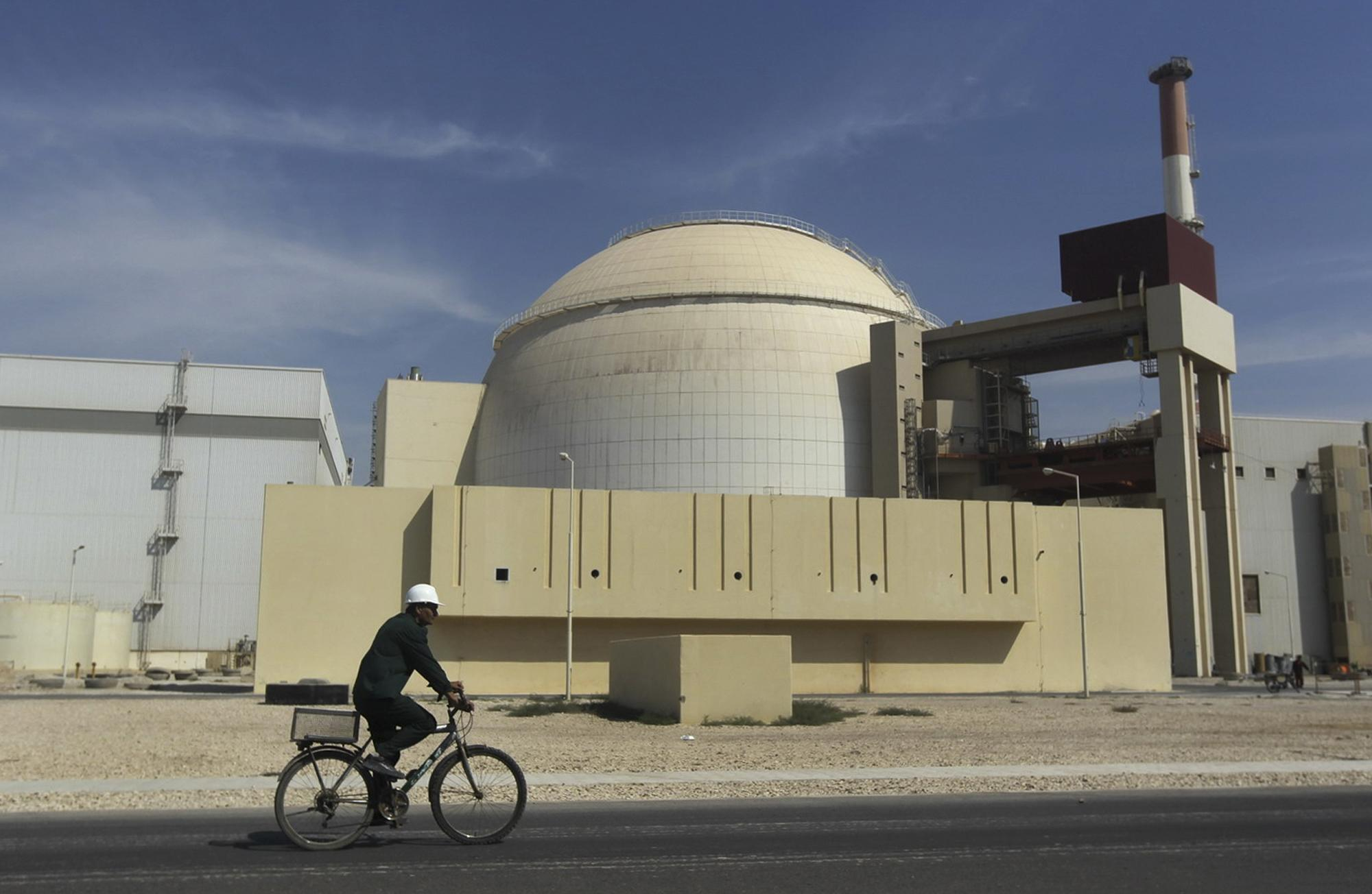 FILE - In this Oct. 26, 2010, file photo, a worker rides a bike in front of the reactor building of the Bushehr nuclear power plant, just outside the southern city of Bushehr, Iran. Several countries monitoring Iran's nuclear program have picked up information that the country's only power-producing nuclear reactor was damaged by one or more of several recent earthquakes, with long cracks appearing in at least one section of the structure, two diplomats said Tuesday June 4, 2013. (AP Photo/Mehr News Agency, Majid Asgaripour, File)