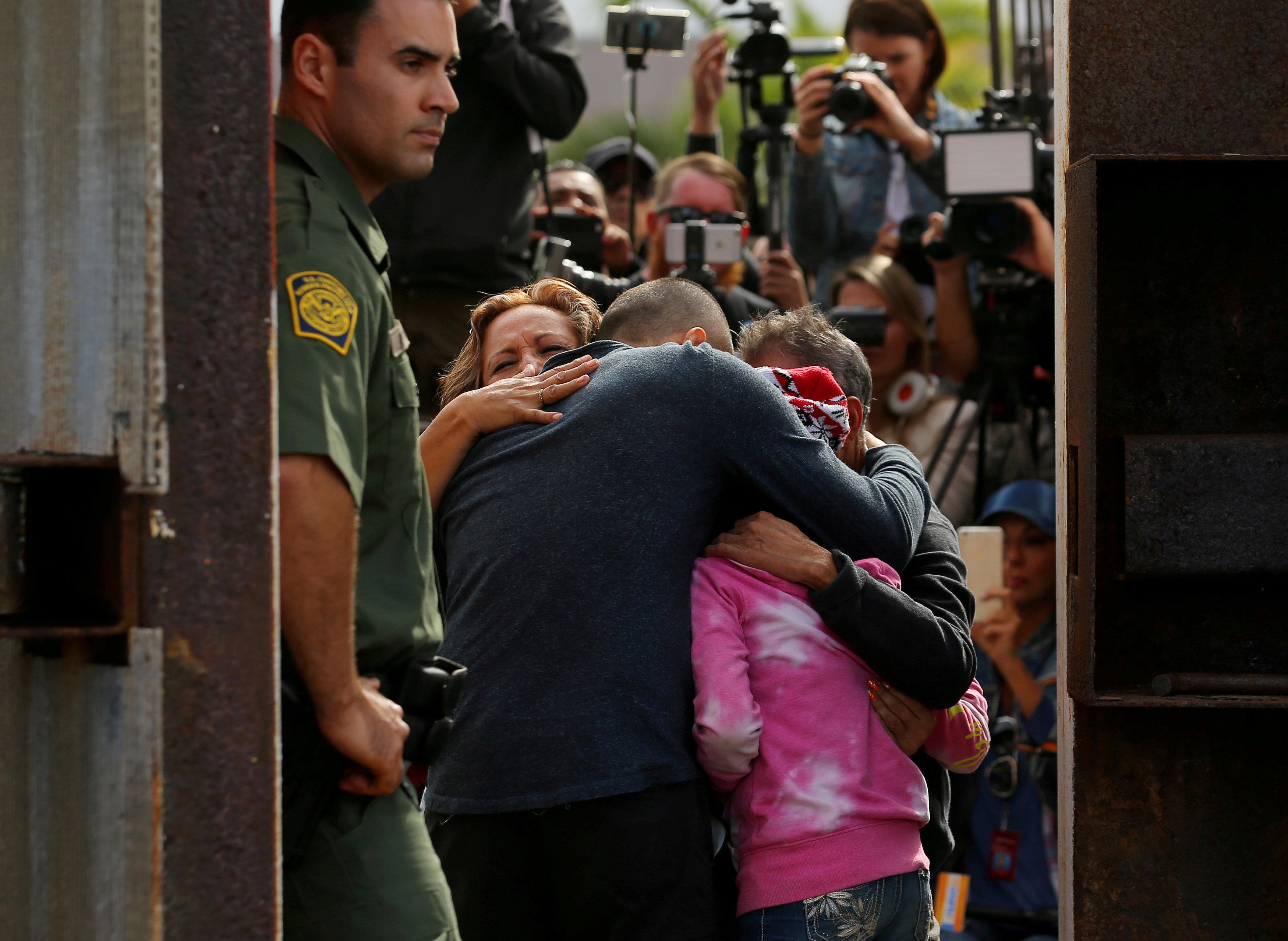 FILE PHOTO - U.S. Border patrol agents stands at an open gate on the fence along the Mexico border to allow Adrian Gonzalez-Morales and his daughter Aileen hug his parents Juan and Martha, as part of Universal Children's Day at the Border Field State Park, California, U.S. on November 19, 2016. REUTERS/Mike Blake/File Photo