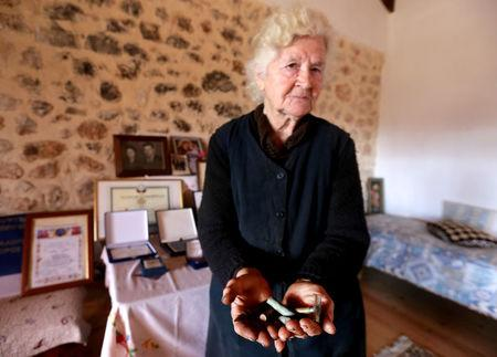 Ermioni Brigo, 85, holds bullets, empty shells and an old razor thought to belong to Greek World War Two soldiers in Himara, Albania January 26, 2018. Picture taken January 26, 2018. REUTERS/Florion Goga