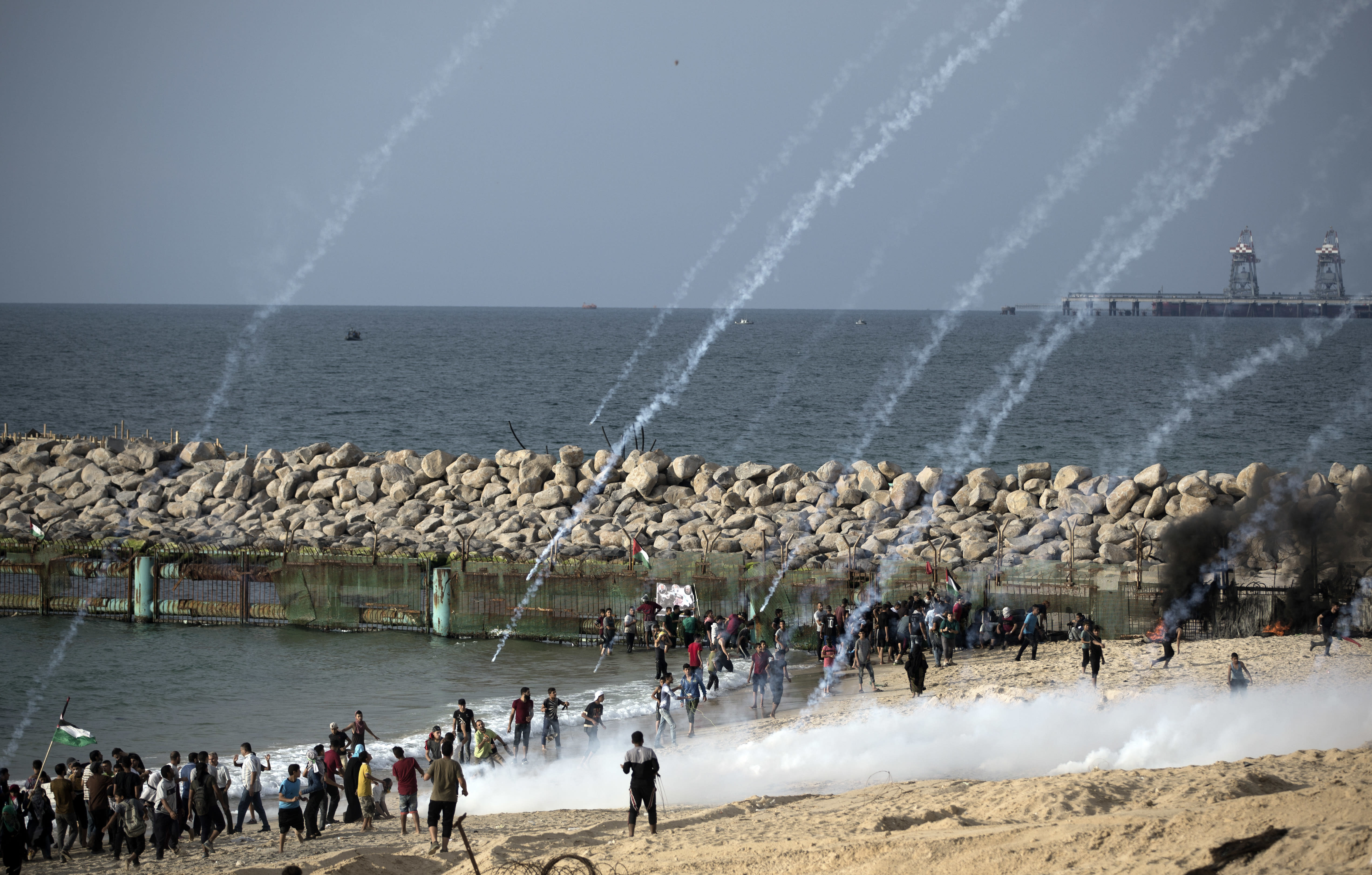Teargas canisters fired by Israeli troops fall over Palestinians during a protest on the beach at the border with Israel near Beit Lahiya, northern Gaza Strip, Monday, Oct. 15, 2018.(AP Photo/Khalil Hamra)