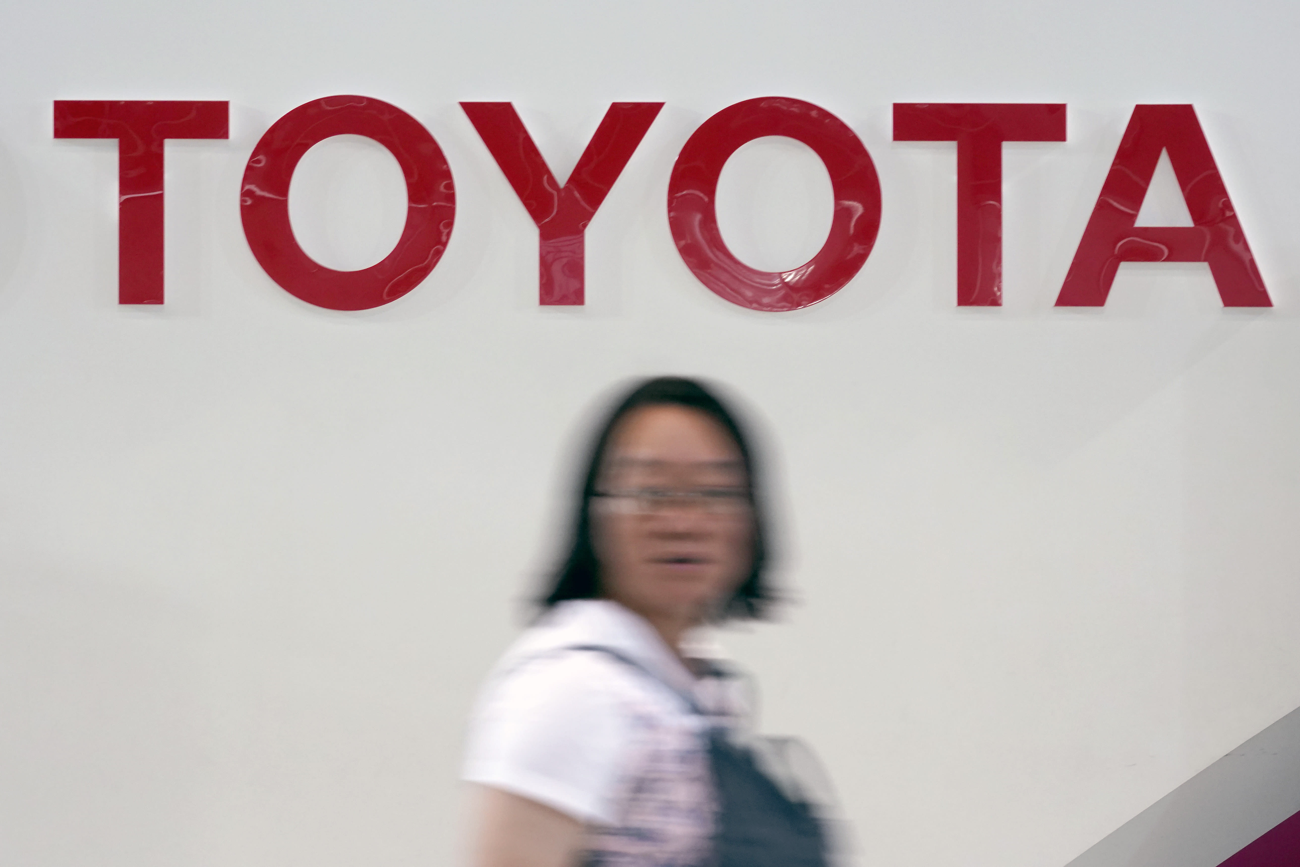 FILE - In this Aug. 2, 2019, file photo, a visitor walks by the logo of Toyota at a show room in Tokyo. Japan's top automaker Toyota has seen a 1% rise in July-September profit as vehicle sales grew around the world, according to Toyota's report on Thursday, Nov. 7, 2019. (AP Photo/Eugene Hoshiko)