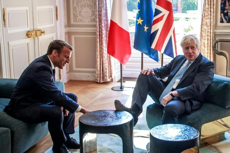 Britain's Prime Minister Boris Johnson places his foot on the table during a meeting with French President Emmanuel Macron (at the Elysee Palace in Paris