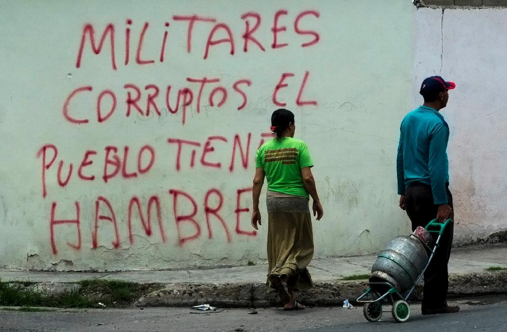"Graffiti in the low income Santa Rita neighborhood in Maracay, 70km from Caracas, reads ""Corrupt military, the people are hungry"" (AFP Photo/Juan Barreto)"