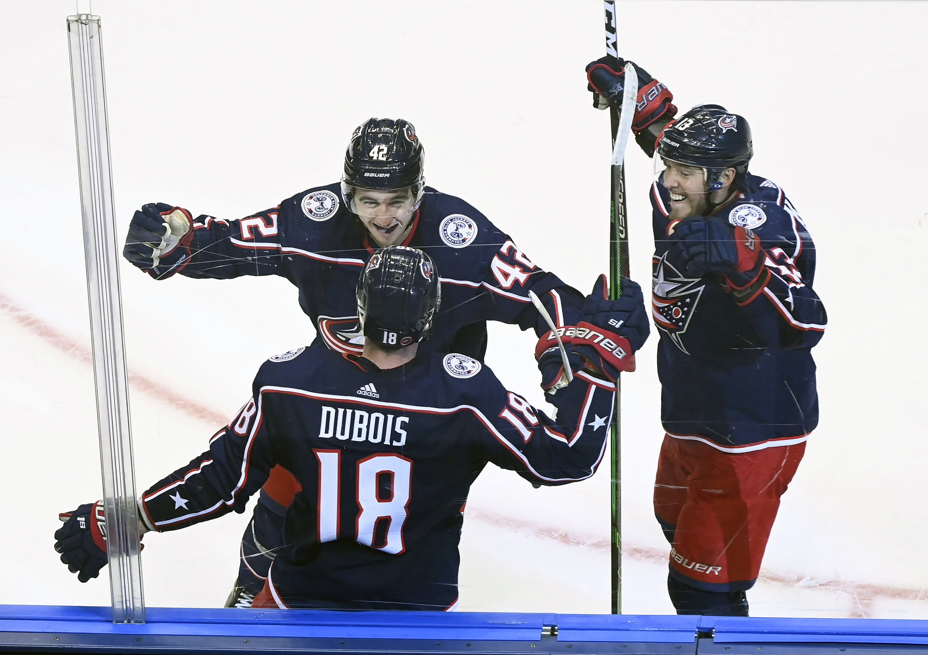 Columbus Blue Jackets center Pierre-Luc Dubois (18) celebrates his game winning goal against the Toronto Maple Leafs with teammates Alexandre Texier (42) and Cam Atkinson (13) during overtime in an NHL hockey playoff game Thursday, Aug. 6, 2020, in Toronto. (Nathan Denette/The Canadian Press via AP)