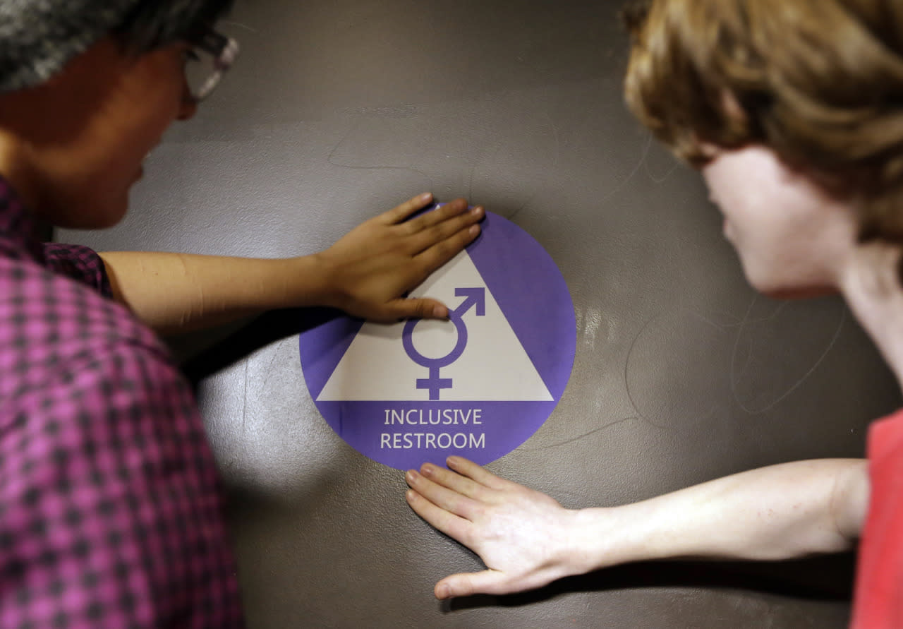 <p>Destin Cramer, left, and Noah Rice place a new sticker on the door at the ceremonial opening of a gender neutral bathroom at Nathan Hale High School on May 17, 2016, in Seattle. President Obama's directive ordering schools to accommodate transgender students has been controversial in some places, but since 2012, Seattle has mandated that transgender students be able to use of the bathrooms and locker rooms of their choice. Nearly half of the district's 15 high schools already have gender neutral bathrooms, and one high school has had a transgender bathroom for 20 years. (Elaine Thompson/AP)</p>