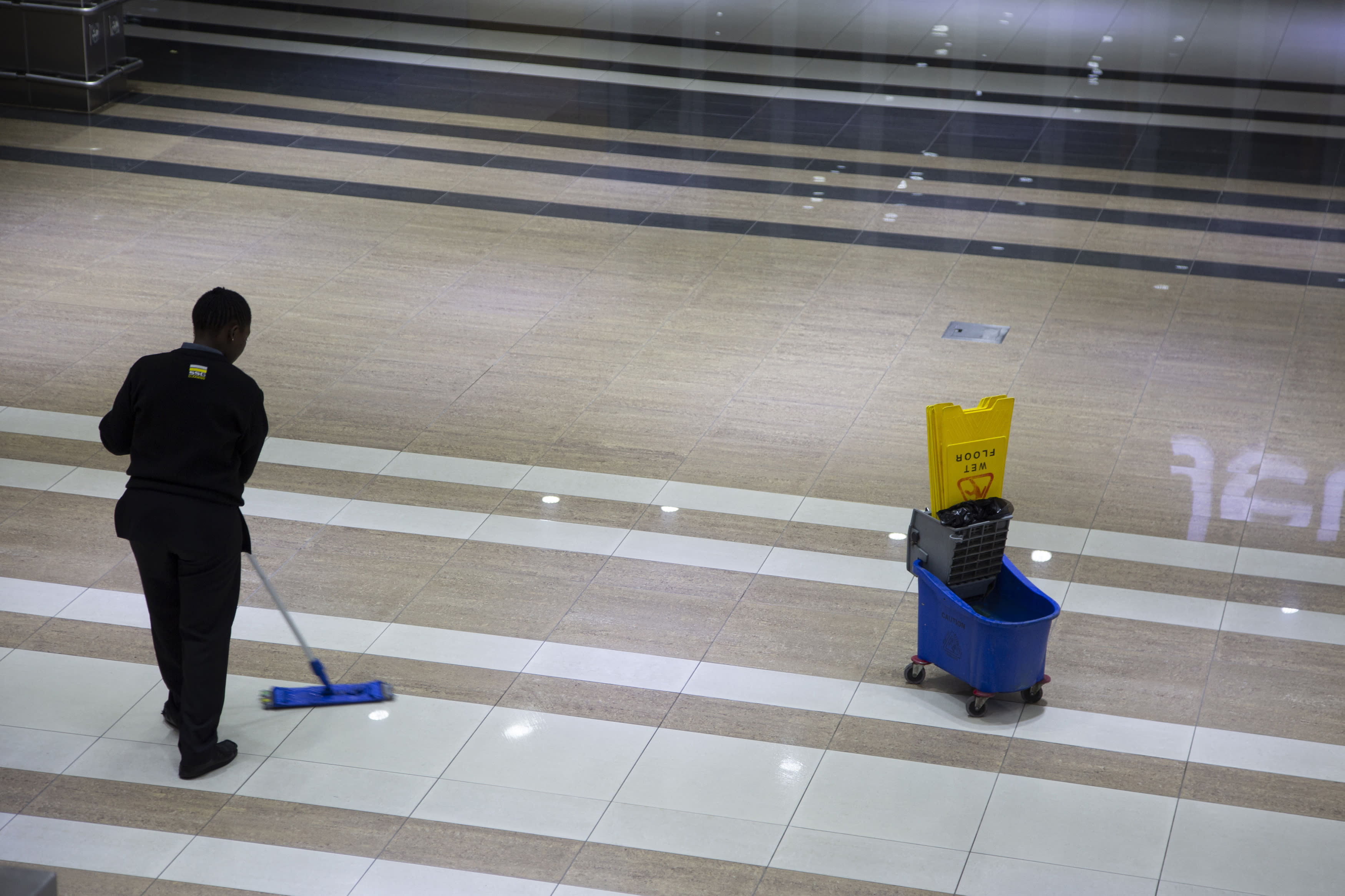 A cleaner mops a floor in a Johannesburg supermarket Wednesday, March 18, 2020 as a measure against the new coronavirus. For most people, the new coronavirus causes only mild or moderate symptoms. For some it can cause more severe illness. (AP Photo/Denis Farrell)