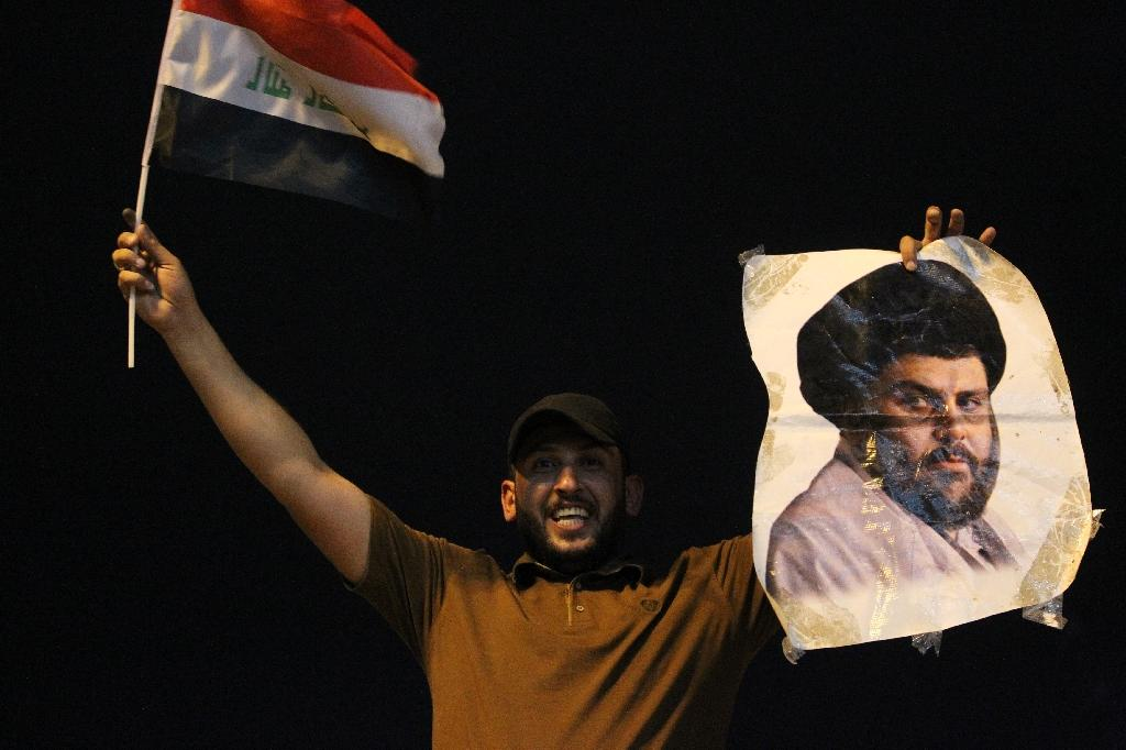 An Iraqi man celebrates with a picture of Shiite cleric Muqtada Sadr during the general election in Baghdad on May 14, 2018 (AFP Photo/AHMAD AL-RUBAYE)