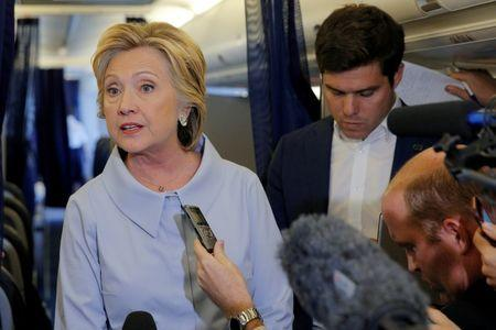 U.S. Democratic presidential candidate Hillary Clinton answers questions from reporters on her campaign plane enroute to a campaign stop in Moline