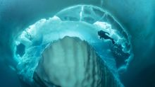 Stunning photos show dive beneath giant iceberg