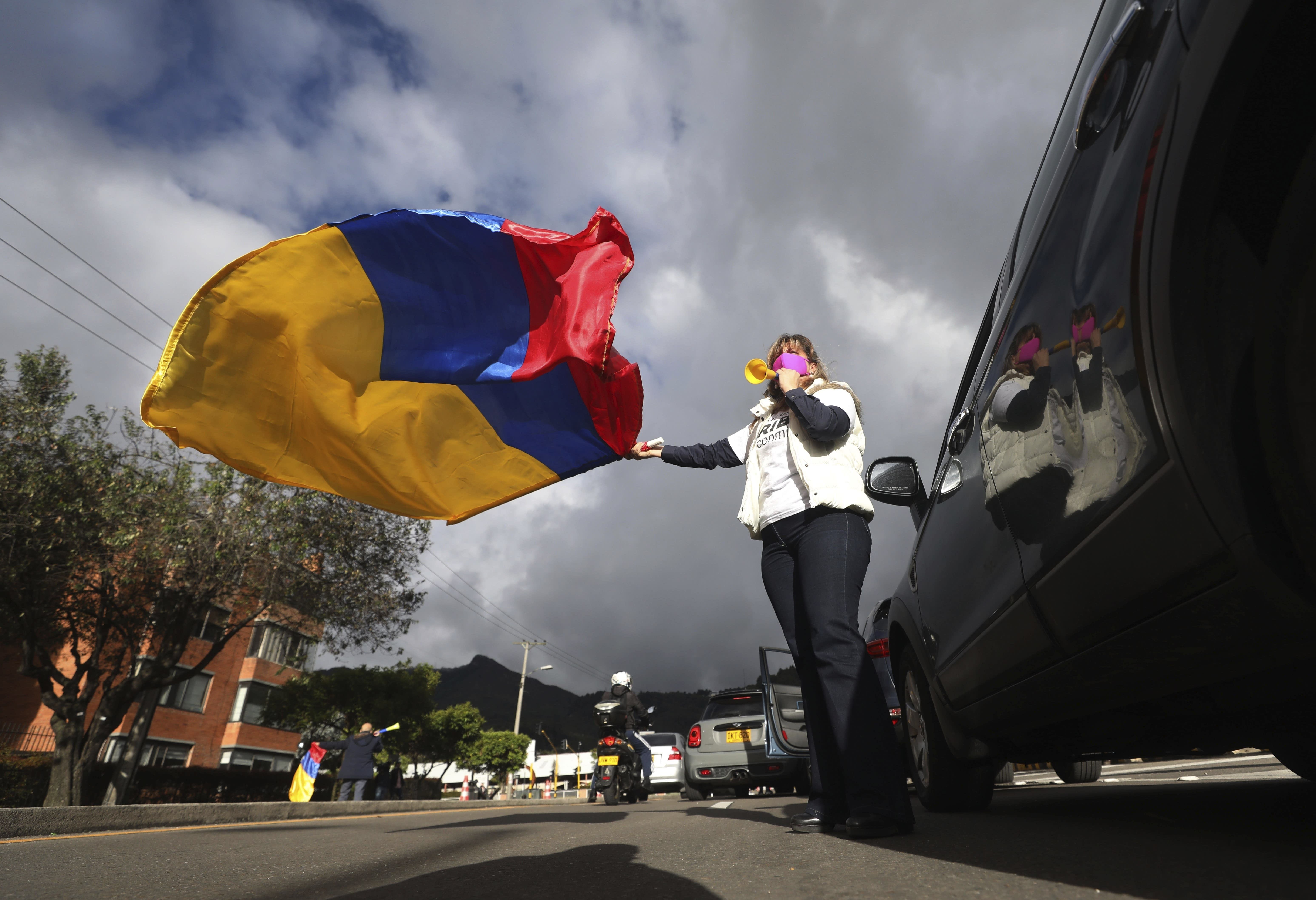 A supporter of former President Alvaro Uribe waving a national flag takes part in a caravan to protest the Supreme Court decision to place Uribe under house arrest while it advances a witness tampering investigation against him, in Bogota, Colombia, Friday, Aug. 7, 2020. (AP Photo/Fernando Vergara)