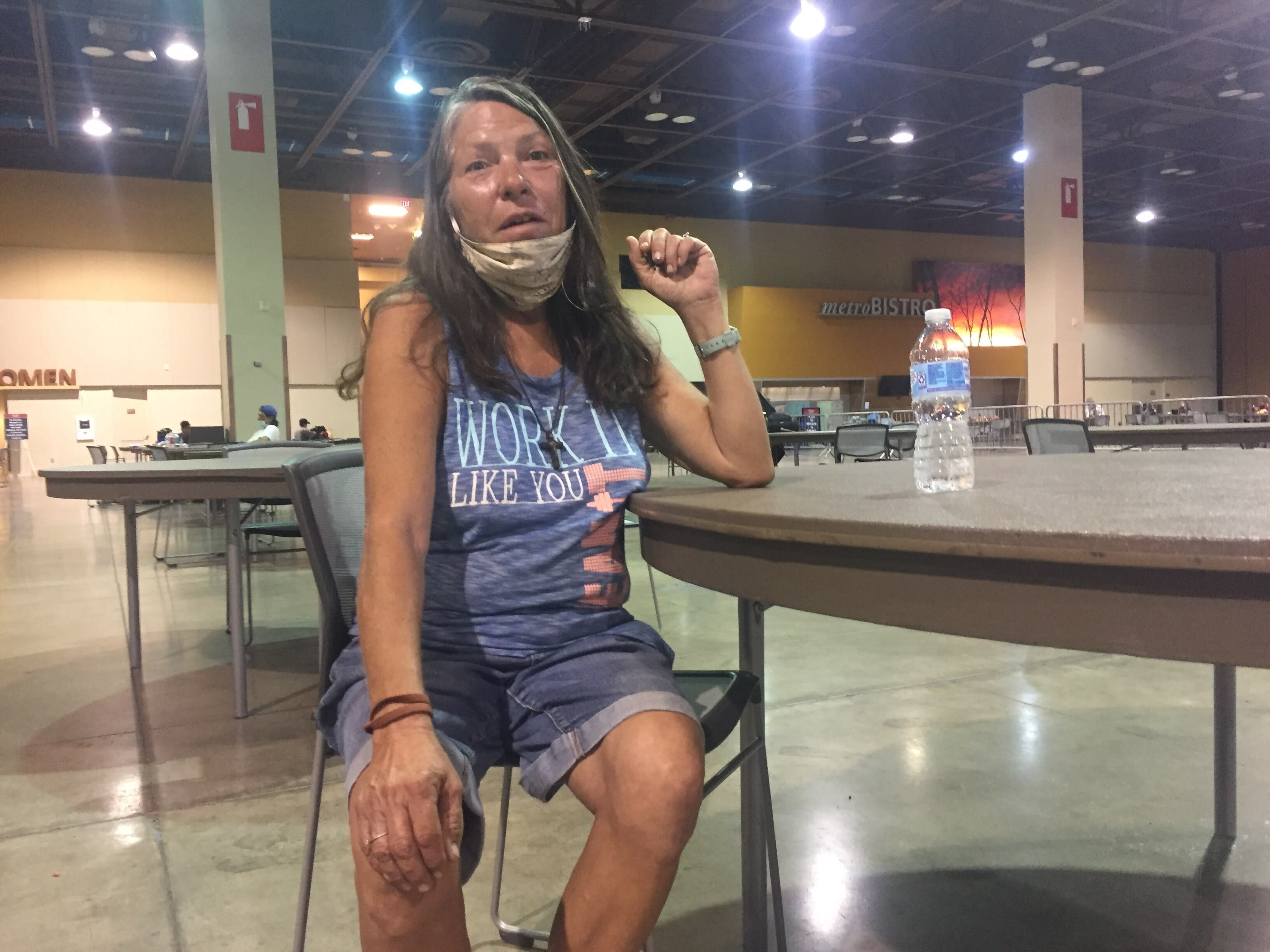 Lena Stewart, 57, receives a water bottle at the heat respite center at the Phoenix Convention Center Sept. 1, 2020. The area can accommodate up to 250 people and since opening in late May officials have recorded more than 17,000 visits. (AP Photo/Brian P.D. Hannon)