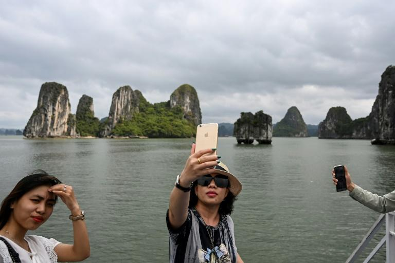 Local tourists take selfies in Ha Long Bay (AFP Photo/Manan VATSYAYANA)