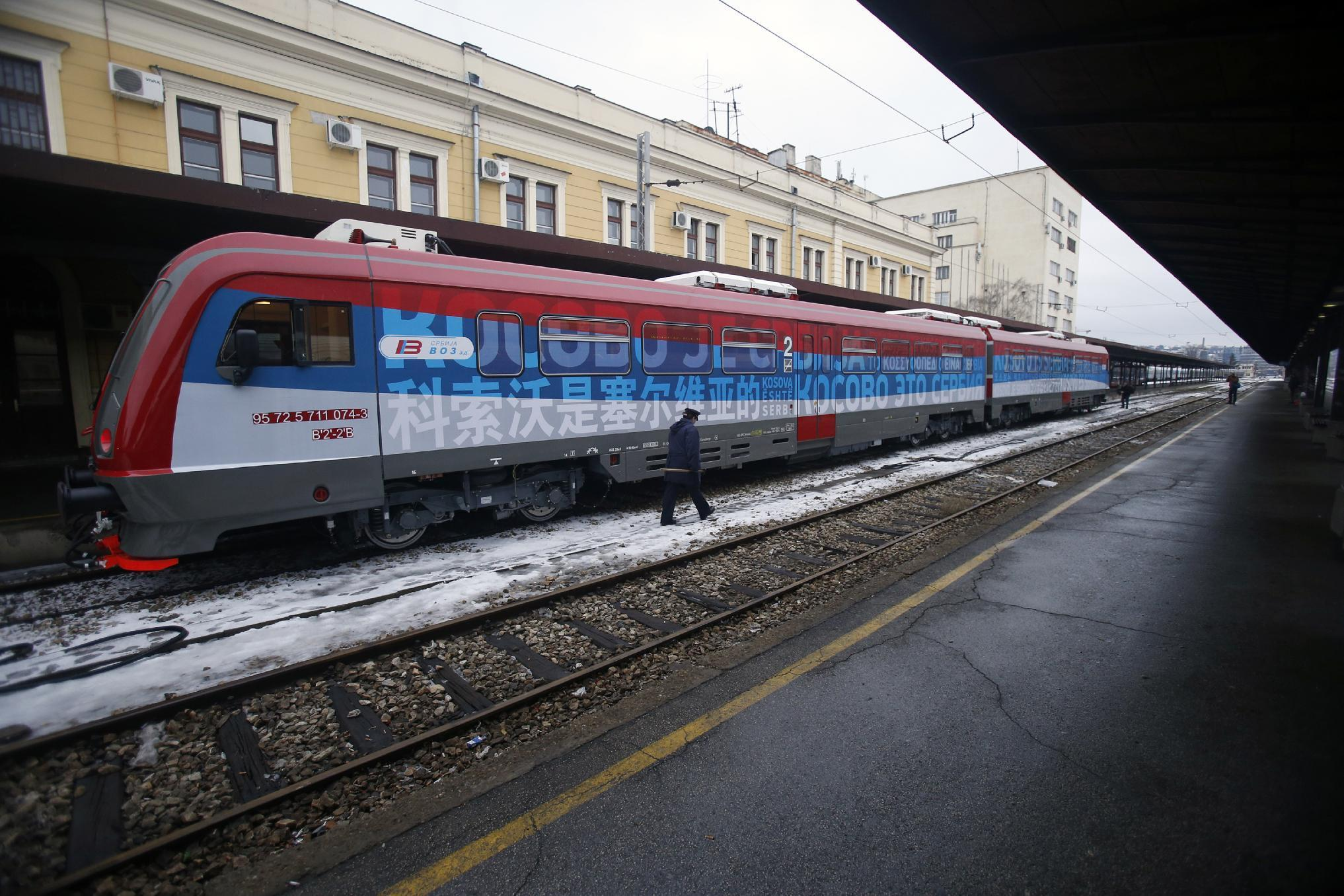 """A railroad worker walks by the first train decorated with letters that read """"Kosovo is Serbian"""" written in twenty languages departing from the Belgrade to Mitrovica, Kosovo at Belgrade's railway station, Serbia, Saturday, Jan. 14, 2017. Serbia has launched a railway link to Serb-dominated northern Kosovo despite protests from authorities in Pristina who described the move as a provocation and an aggressive violation of Kosovo's sovereignty. (AP Photo/Darko Vojinovic)"""