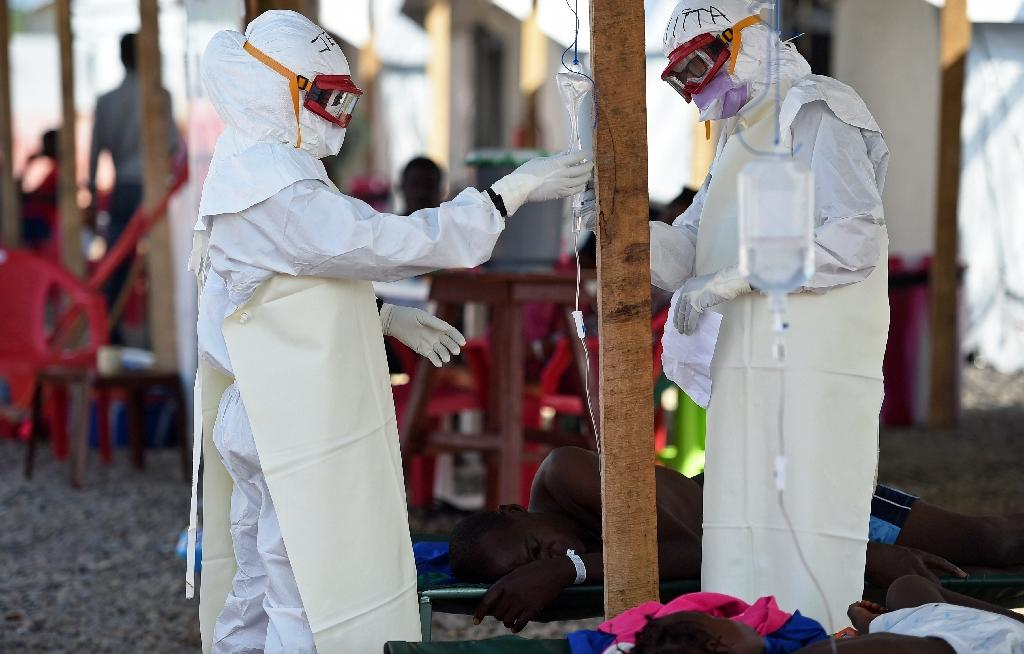 Health workers wearing personal protective equipment assist an Ebola patient at the Kenama treatment centre run by the Red Cross Society on November 15, 2014