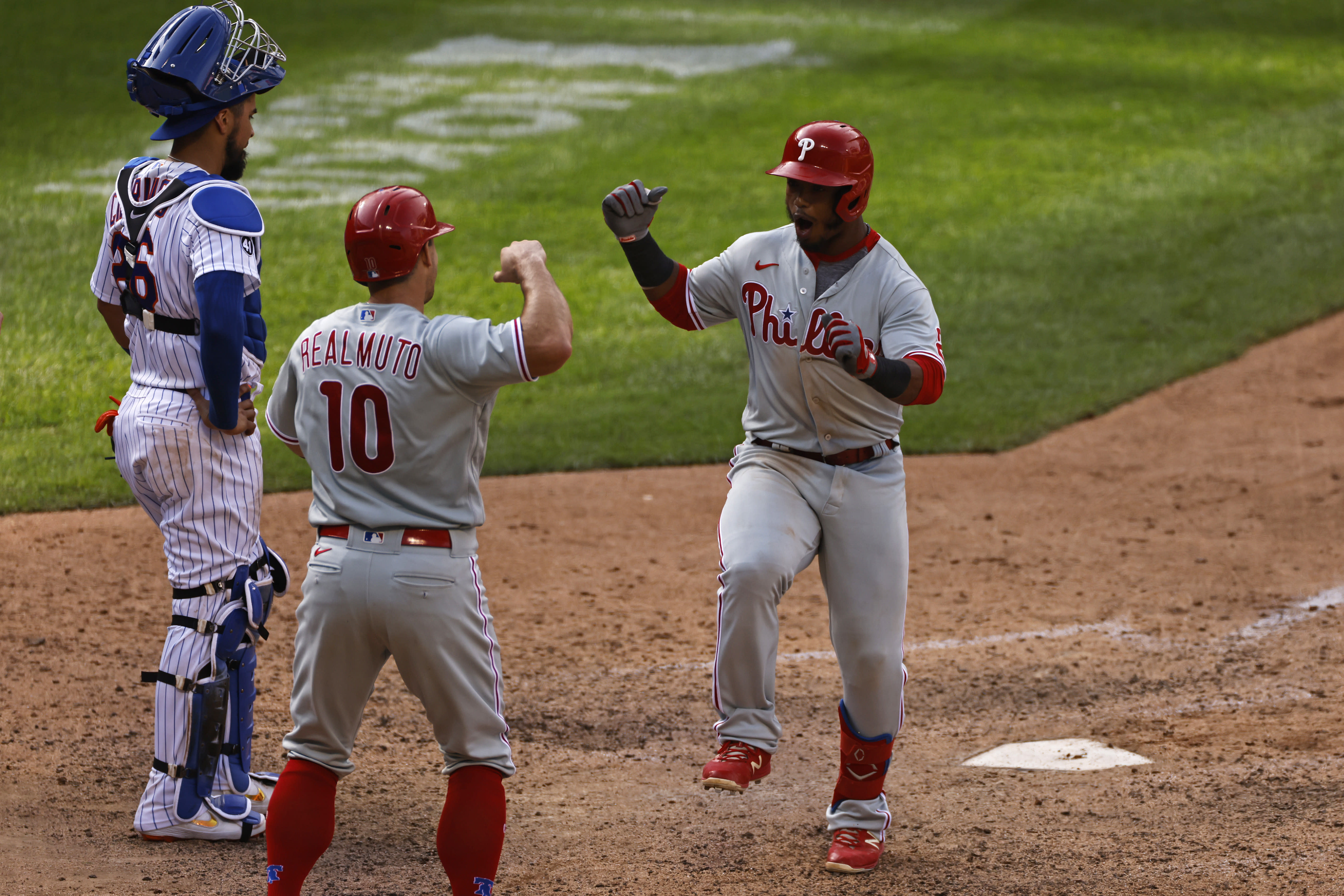 Philadelphia Phillies' Jean Segura celebrates hitting a two-run home run with J.T. Realmuto (10) in front of New York Mets catcher Robinson Chirinos during the 10th inning of a baseball game on Monday, Sept. 7, 2020, in New York. (AP Photo/Adam Hunger)
