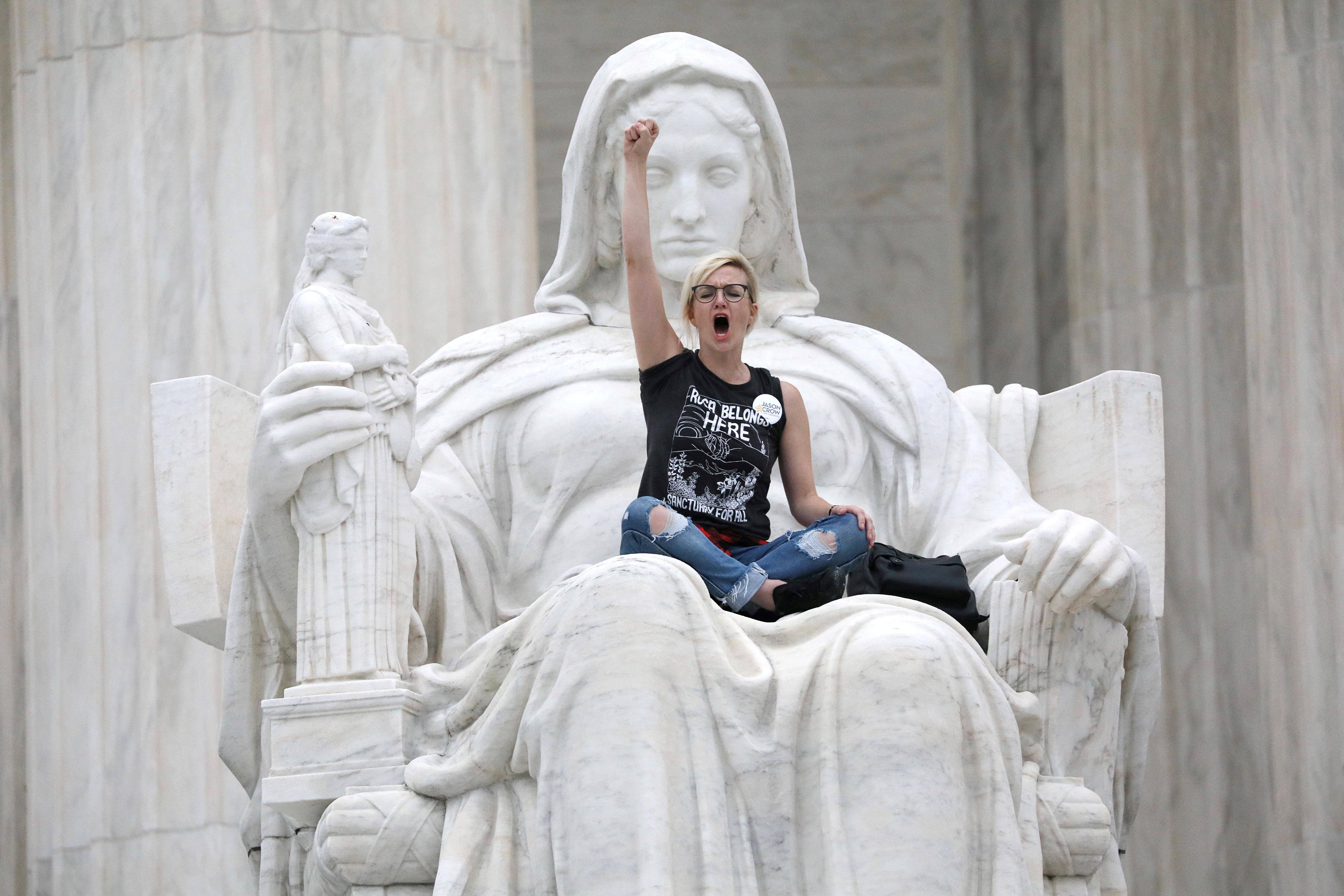 """<p>A protester sits on the lap of """"Lady Justice"""" on the steps of the U.S. Supreme Court building as demonstrators storm the steps and doors of the Supreme Court while Judge Brett Kavanaugh is being sworn in as an Associate Justice of the court inside on Capitol Hill in Washington, D.C., Oct. 6, 2018. (Photo: Jonathan Ernst/Reuters) </p>"""