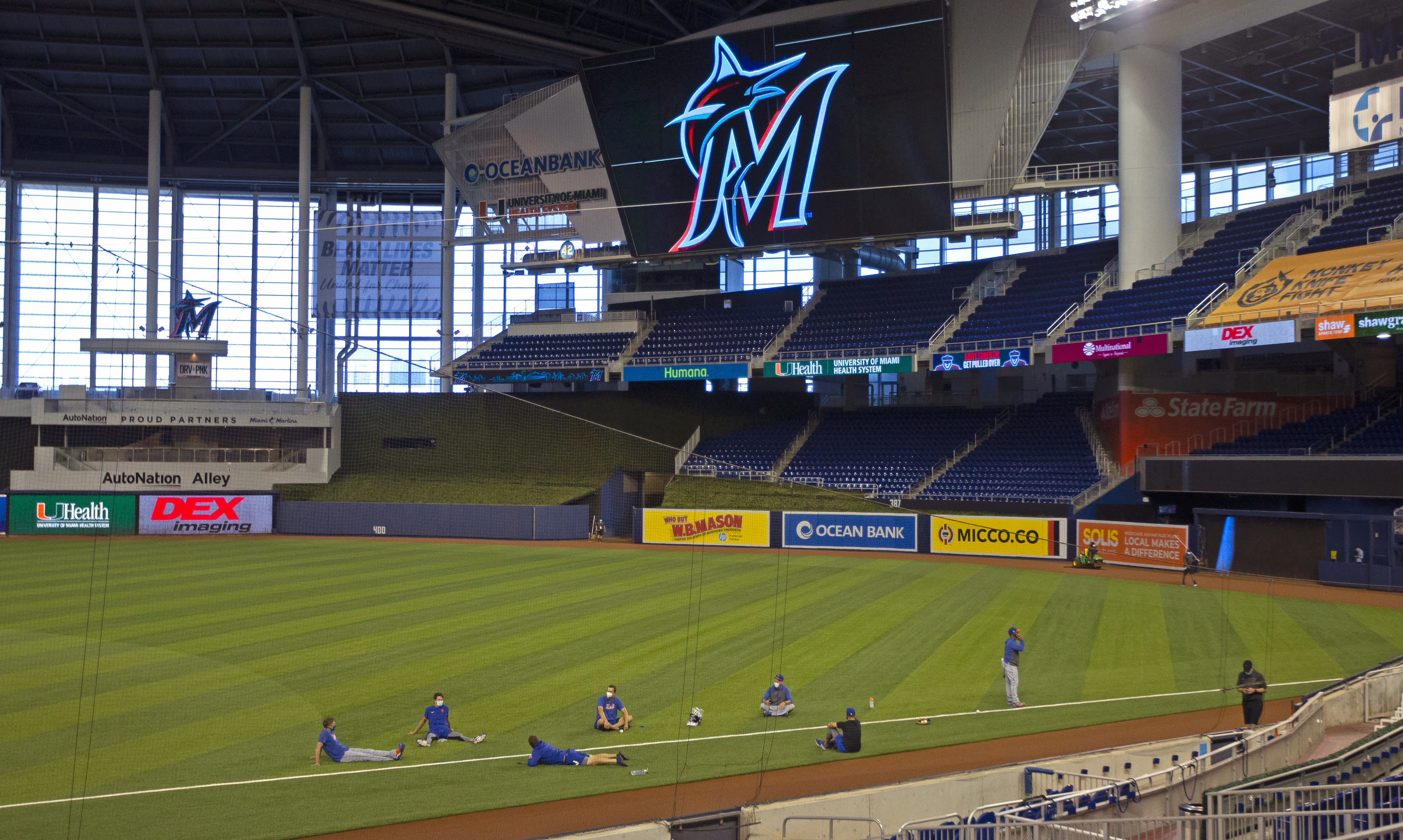 New York Mets players sit on the field before a baseball game against the Miami Marlins, Thursday, Aug. 20, 2020, in Miami. Major League Baseball says the Mets have received two positive tests for COVID-19 in their organization, prompting the postponement of two games against the Marlins. (David Santiago/Miami Herald via AP)