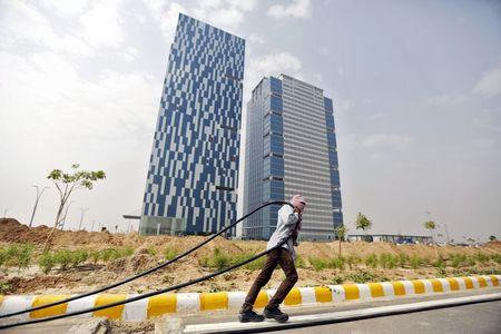 A labourer pulls a cable in front of two office buildings in Gujarat International Finance Tec-City (GIFT) at Gandhinagar, in the western Indian state of Gujarat, April 10, 2015. REUTERS/Amit Dave