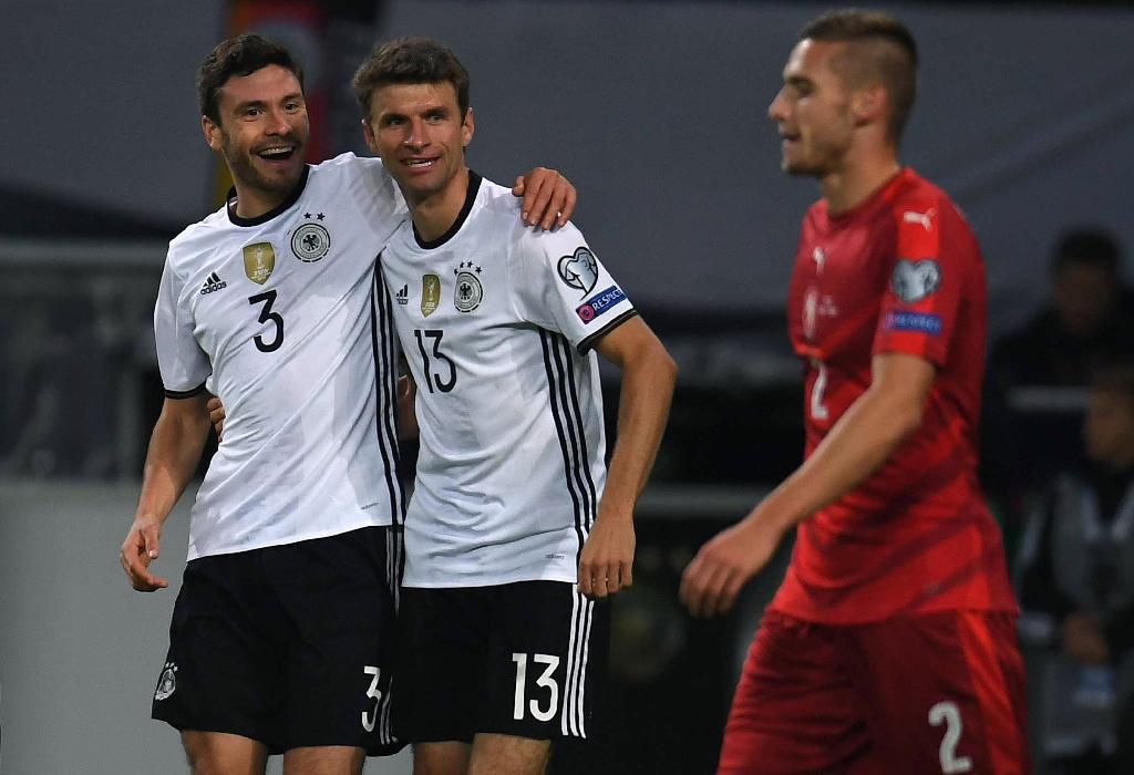 Germany's Thomas Mueller (C) is congratulated by teammate Jonas Hector after scoring a goal during their 2018 World Cup qualifier match against Czech Republic, in Hamburg, on October 8, 2016 (AFP Photo/Patrik Stollarz)