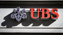 UBS profit falls 11% as it braces for jump in losses