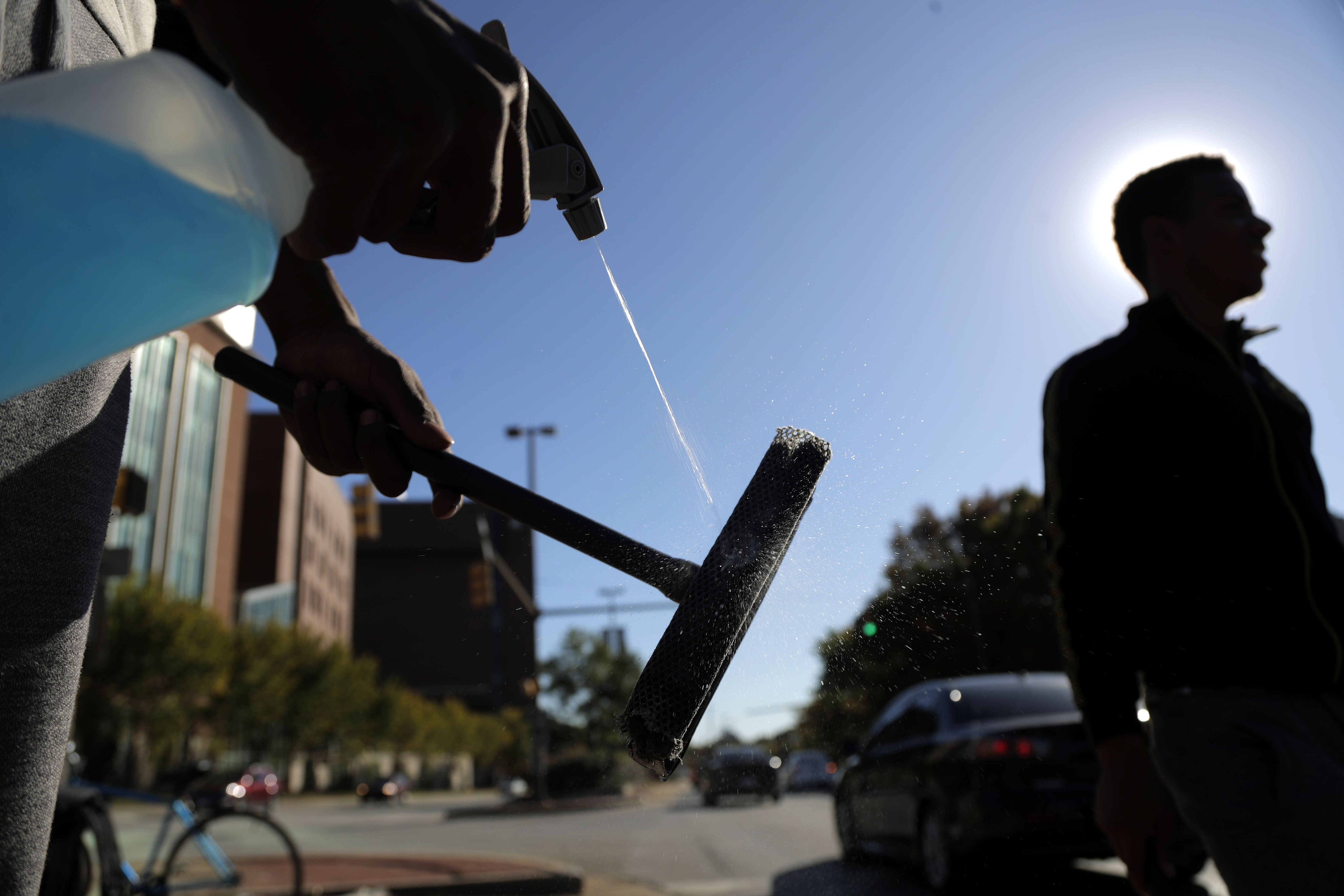 In a photo taken Thursday, Oct. 24, 2019, Jerome Holloway, left, sprays his squeegee as he and another teenager walks by as they work a corner in Baltimore. A debate over Baltimore's so-called squeegee kids is reaching a crescendo as the city grapples with issues of crime and poverty and a complicated history with race relations. Officials estimate 100 squeegee kids regularly work at intersections citywide, dashing into the street as red lights hit to clean windshields in exchange for cash from drivers. (AP Photo/Julio Cortez)