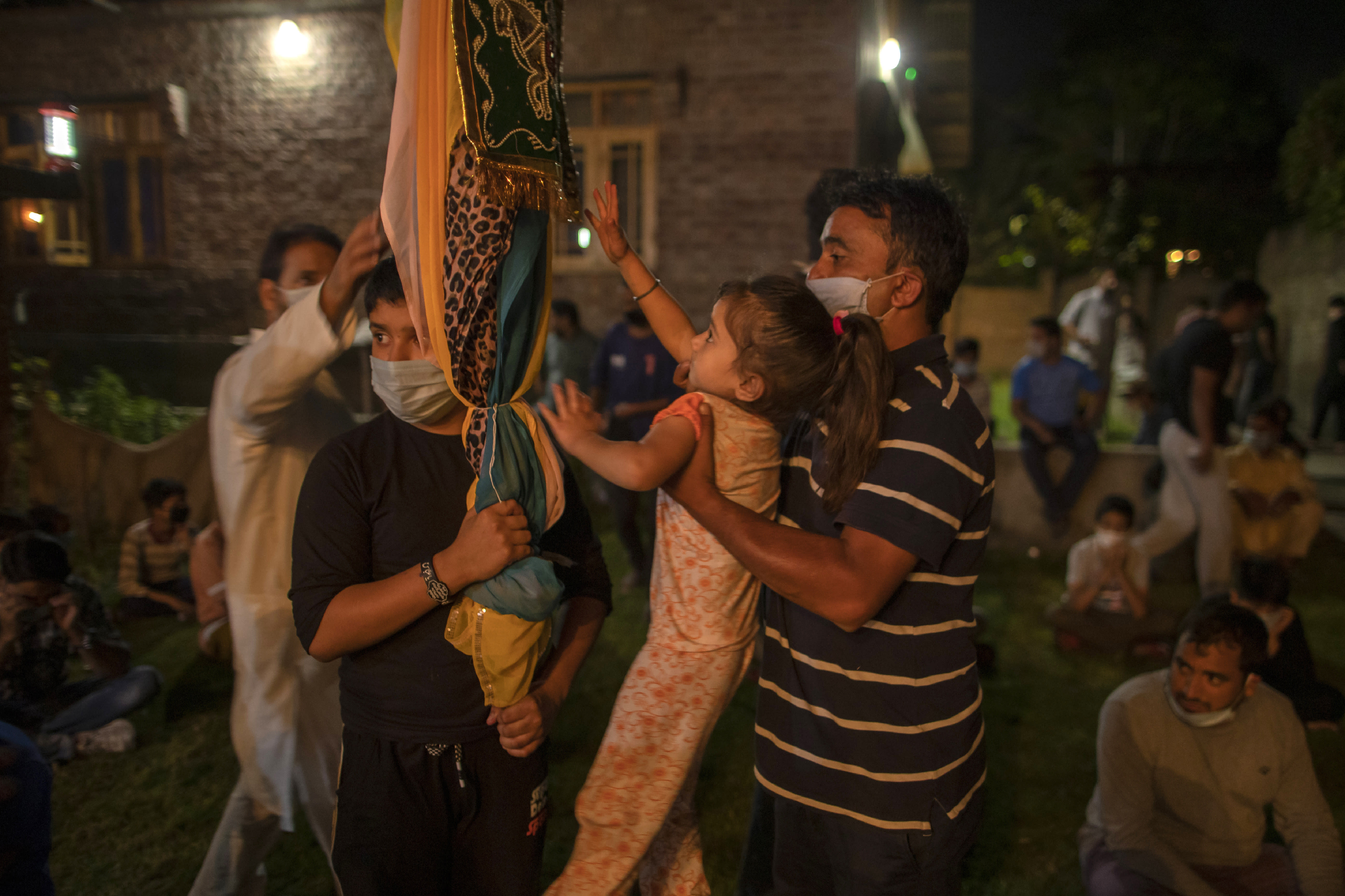 A Kashmiri Shiite Muslim helps her daughter to touch the religious flag at of the ceremony commemorating Muharram inside the lawn of a residential house in Srinagar Indian-controlled Kashmir, Friday, Aug. 21, 2020. Observing the Muslim month of Muharram, which marks the martyrdom of the Prophet Muhammad's grandson in the battle of Karbala, is an article of faith. But as the coronavirus spreads in Indian-controlled Kashmir, Shiite Muslims prefer to commemorate the holy days inside their home following the advice of religious scholars and health experts in the disputed region's main city. (AP Photo/ Dar Yasin)