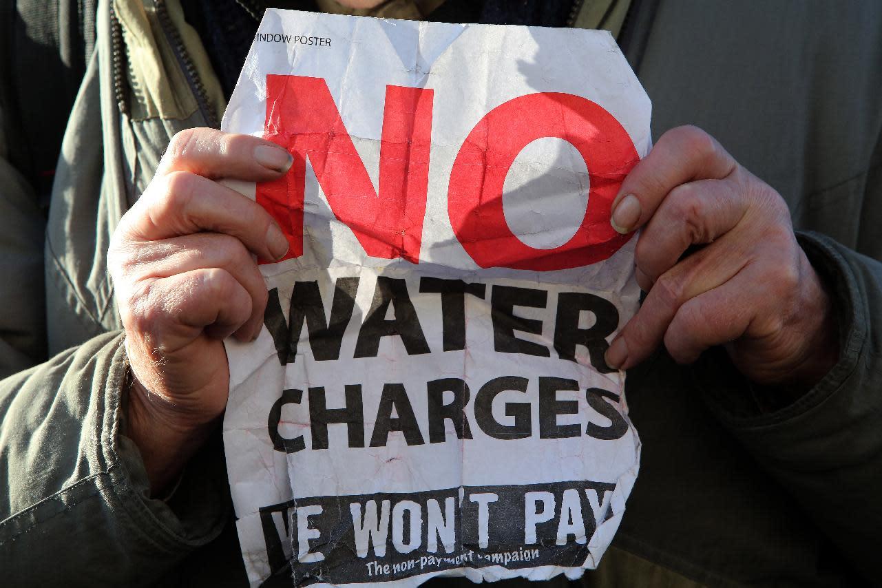 A man holds an anti-water austerity sign in Dublin city centre on January 31, 2014 (AFP Photo/Paul Faith)