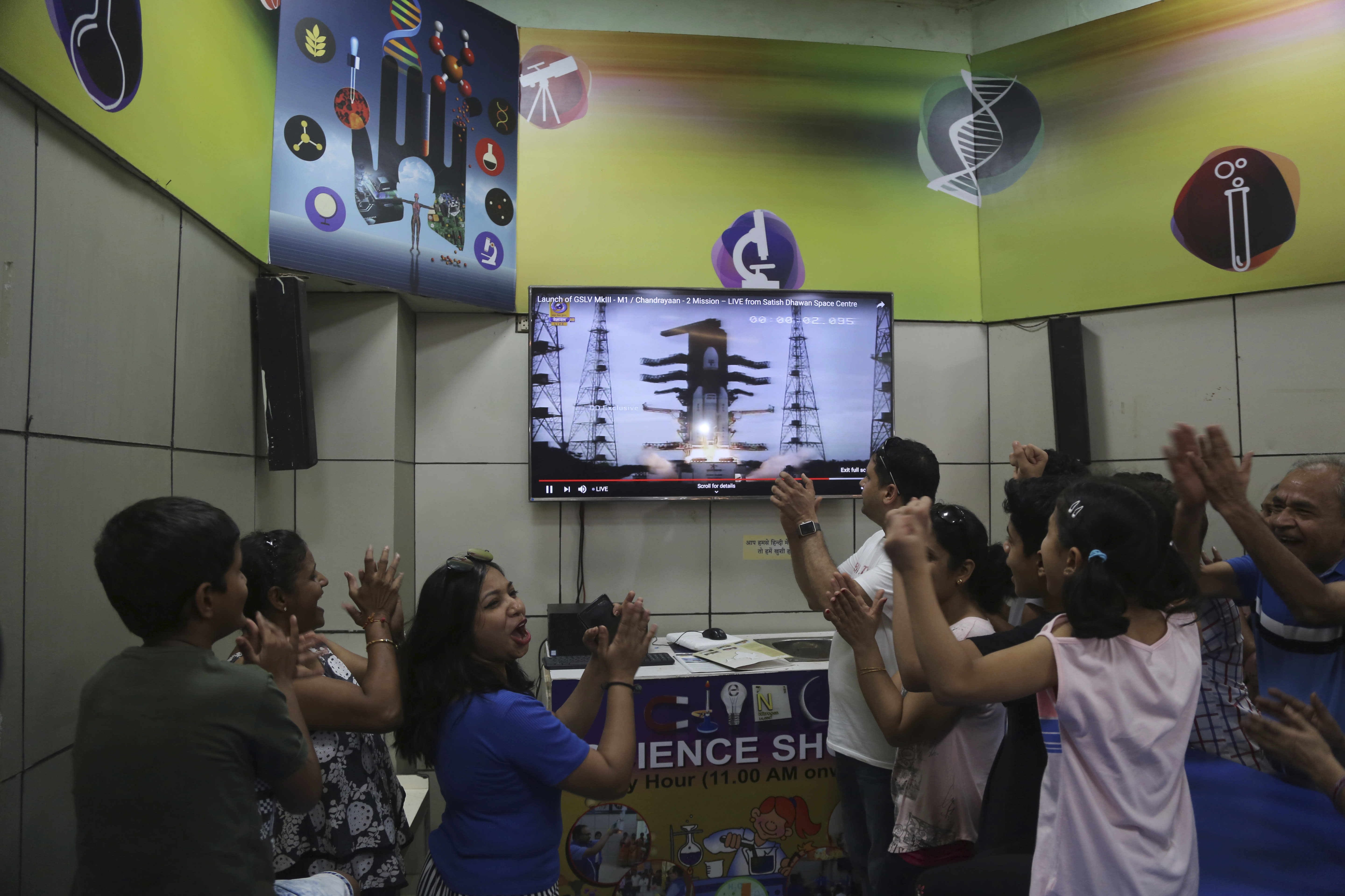 Indians cheer as they watch the on screen the lift off of Indian Space Research Organization (ISRO)'s Geosynchronous Satellite launch Vehicle (GSLV) MkIII carrying Chandrayaan-2 in Mumbai, India, Monday, July 22, 2019. India successfully launched an unmanned spacecraft to the far side of the moon on Monday, a week after aborting the mission due to a technical problem. (AP Photo/Rafiq Maqbool)