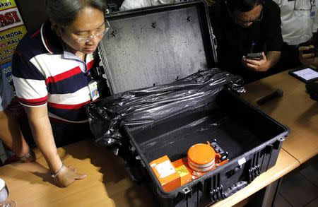 An Indonesian official looks at the cockpit voice recorder of AirAsia QZ8501 during news conference at the National Transportation Safety Committee office in Jakarta January 13, 2015. REUTERS/Pius Erlangga