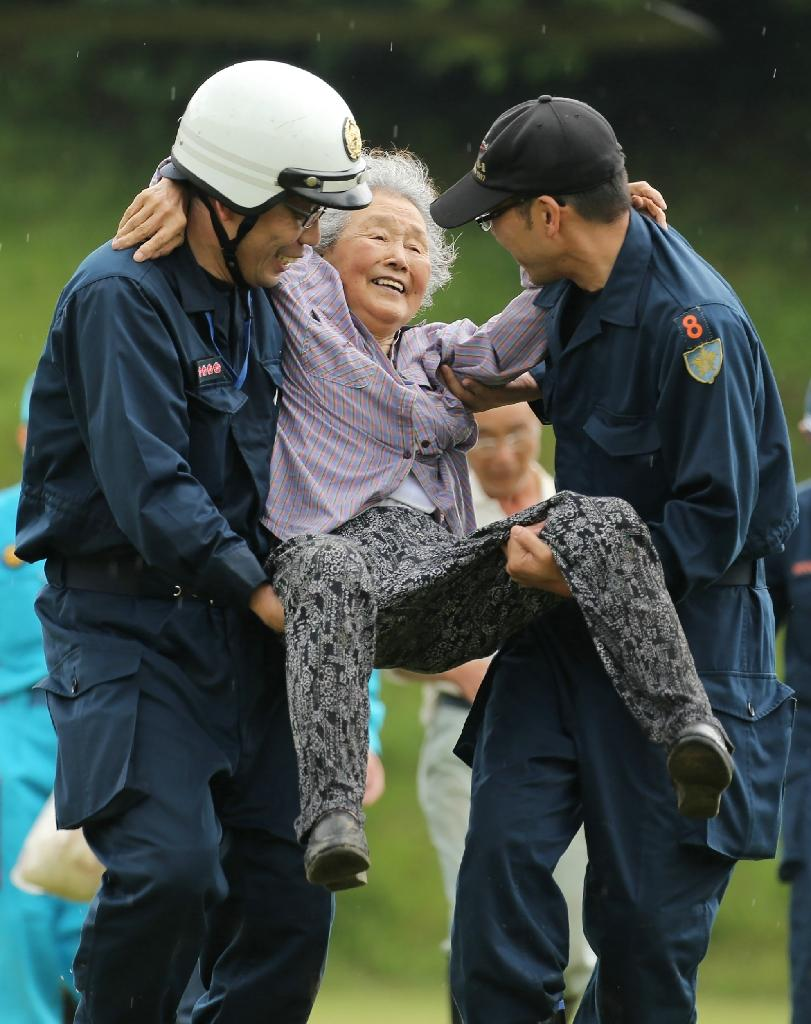 An elderly woman is helped by police officers after being evacuated by a military helicopter from a disaster area following heavy flooding in Asakura, Fukuoka prefecture. (AFP Photo/STR)